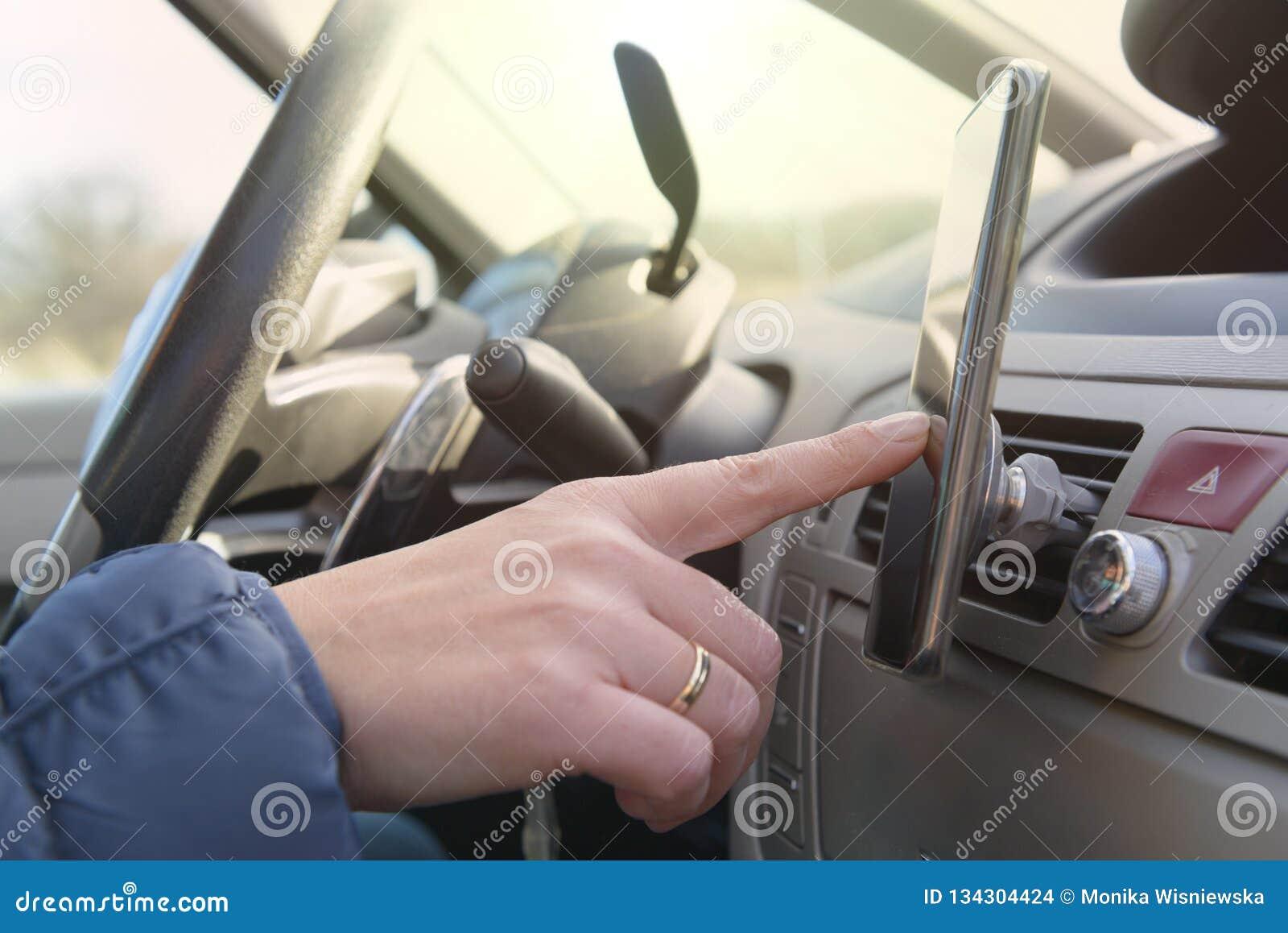 Vrouw die smartphone met behulp van terwijl het drijven van de auto