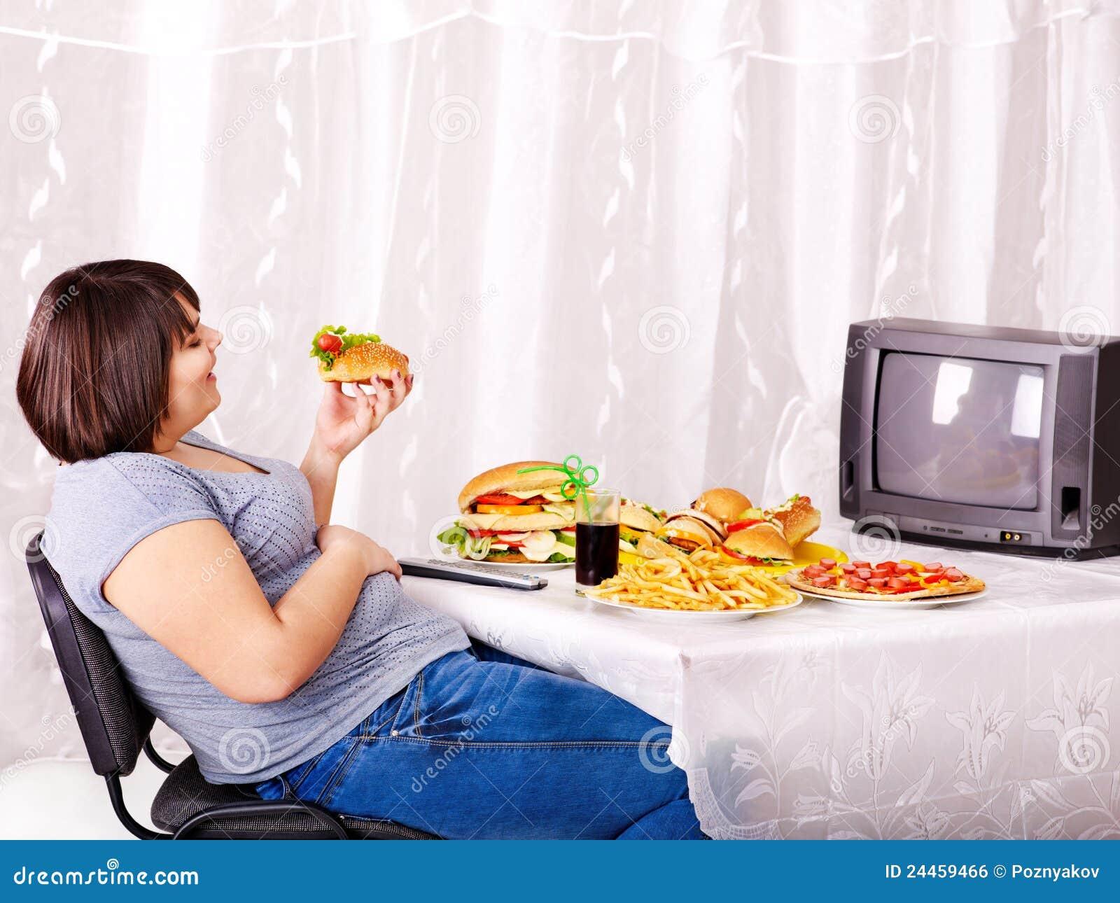 Vrouw die snel voedsel eet en op TV let.