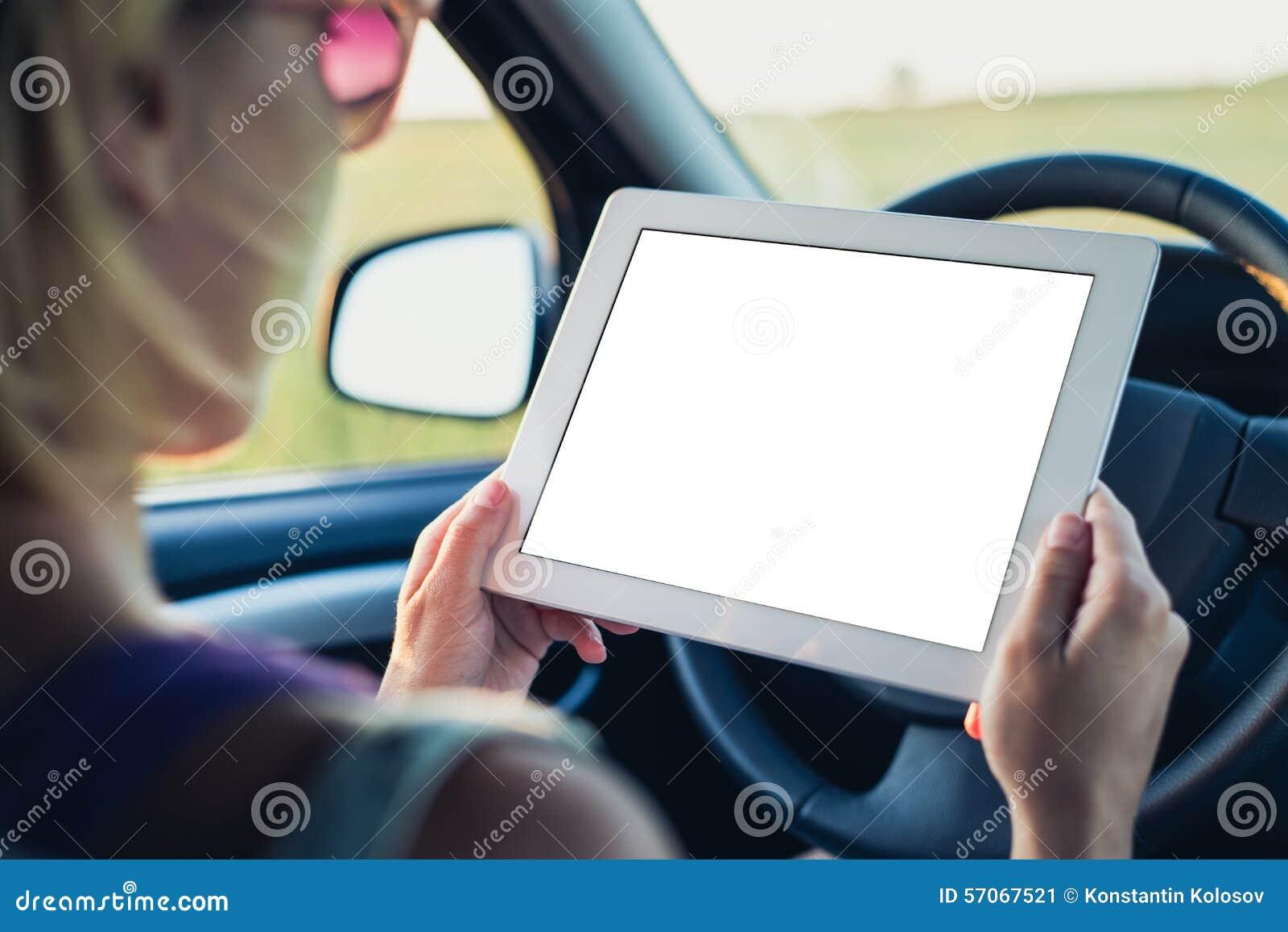 Vrouw die tabletPC in de auto met behulp van