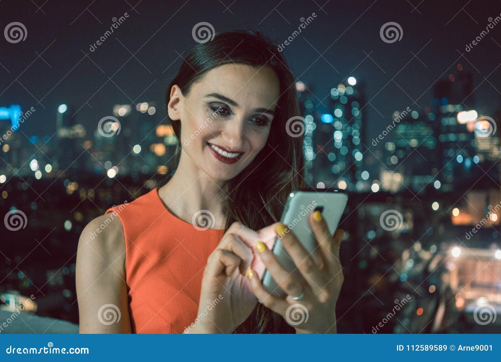 Vrouw die telefoon voor sociale media in het stedelijke plaatsen met behulp van