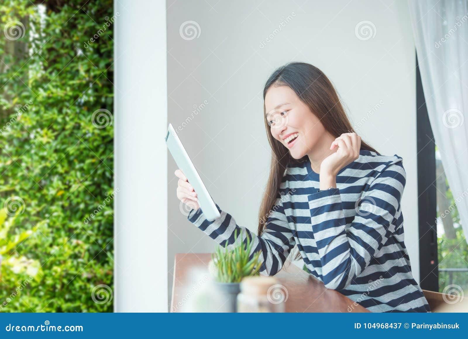 Vrouw die terwijl het gebruiken van tabletcomputer glimlachen