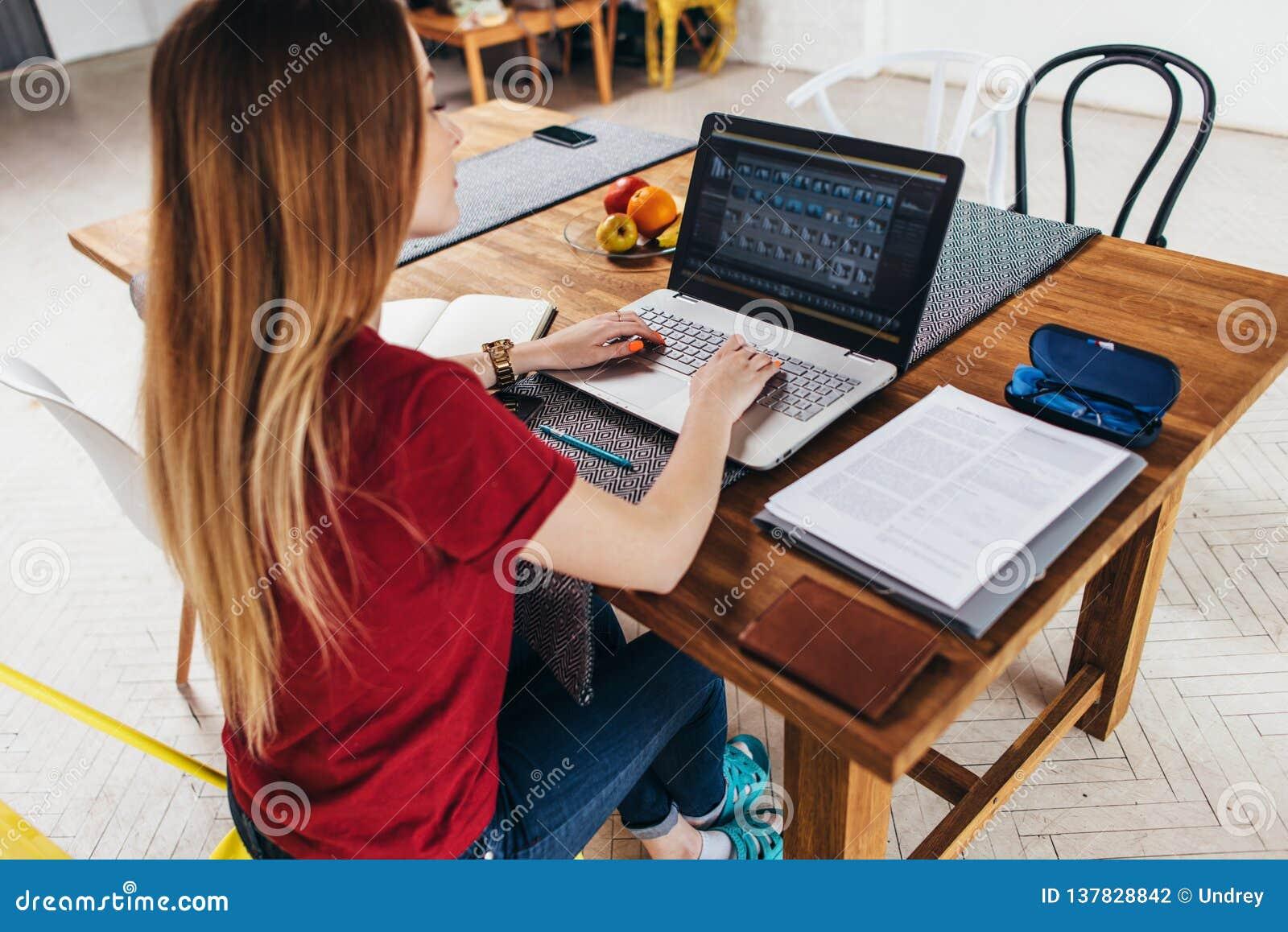Vrouw die thuis gebruikend laptop zitting bij lijst in keuken, freelancer werkend aan notitieboekje werken