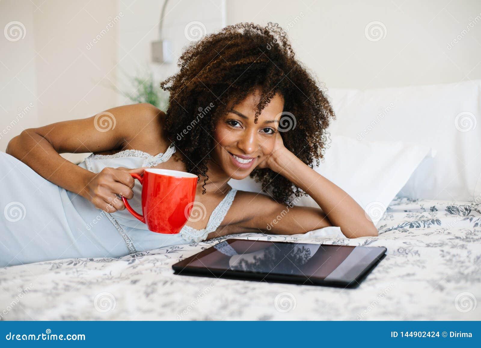 Vrouw die thuis op digitale tablet lezen
