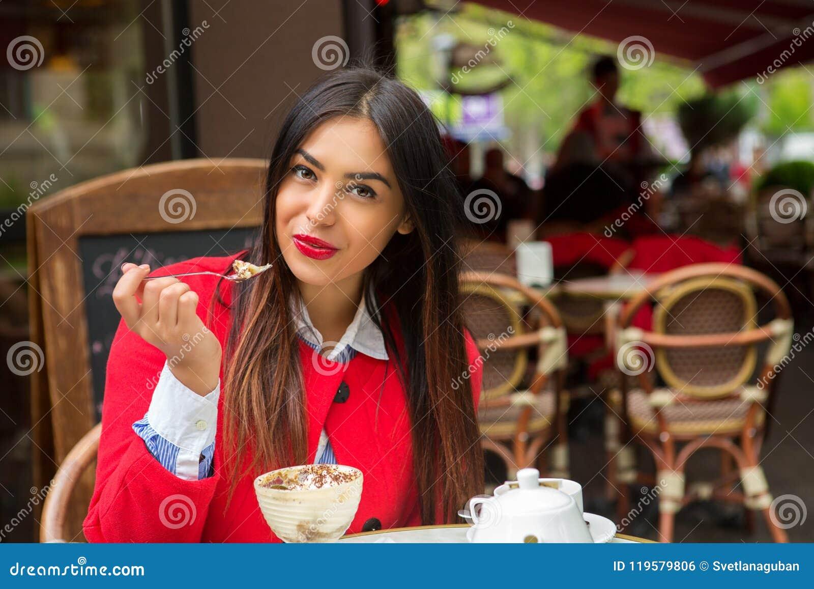 Vrouw die tiramisuwoestijn in een Italiaans restaurant eten