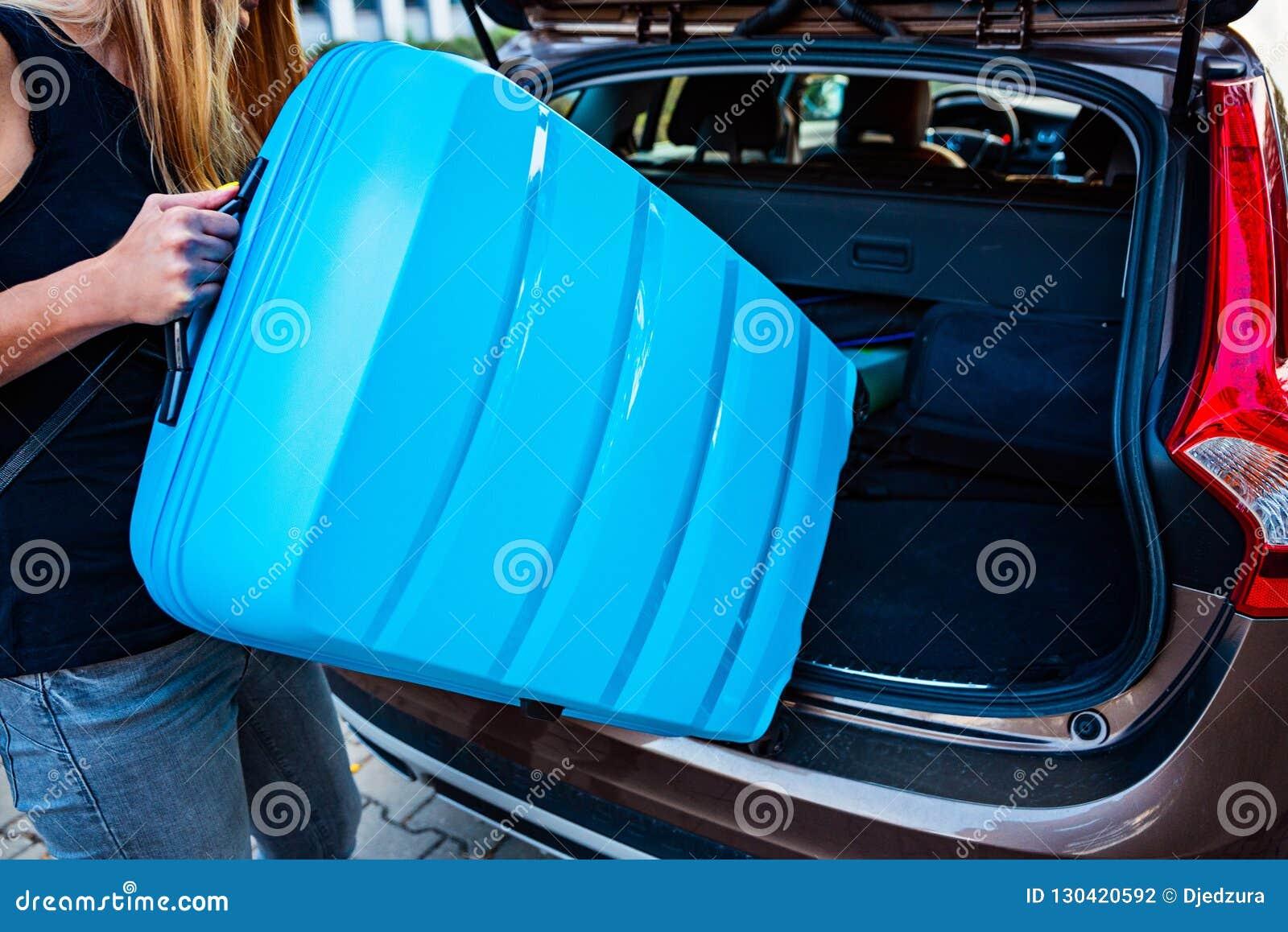 Vrouw die twee blauwe plastic koffers laden aan autoboomstam