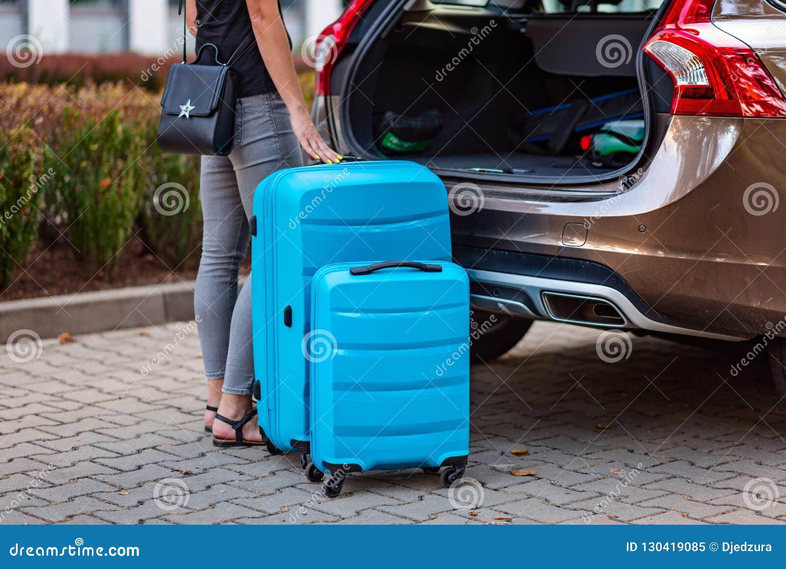 Vrouw die twee blauwe plastic koffers zetten aan autoboomstam