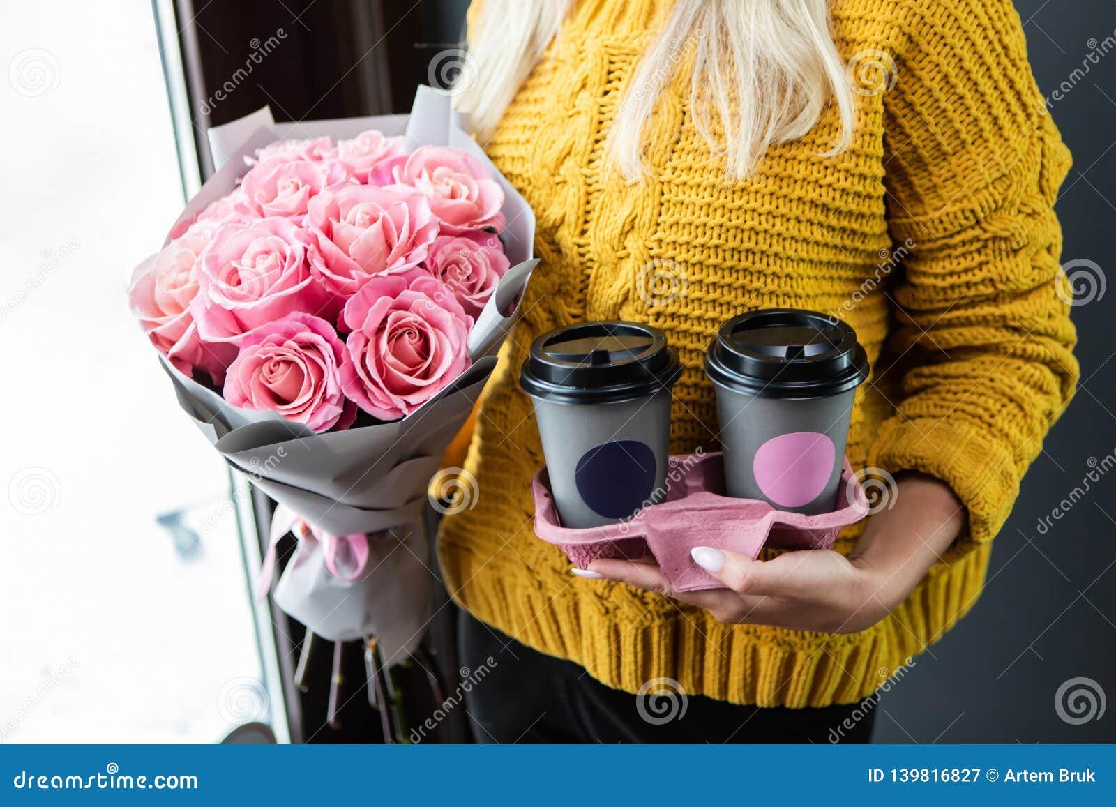 Vrouw die twee koppen van koffie om te gaan en een boeket houden