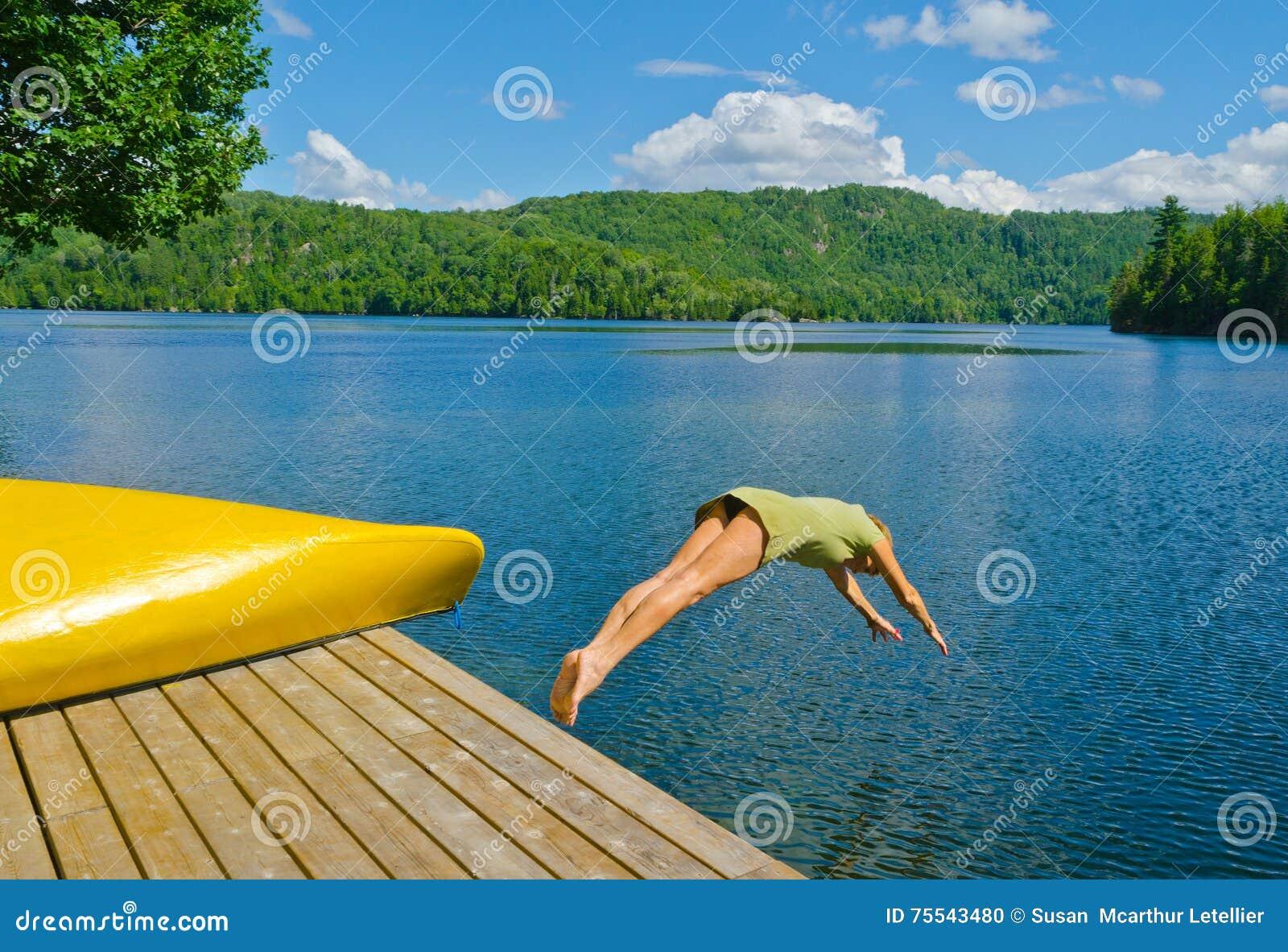 Vrouw die van het dok in meer op een hete de zomerdag duiken