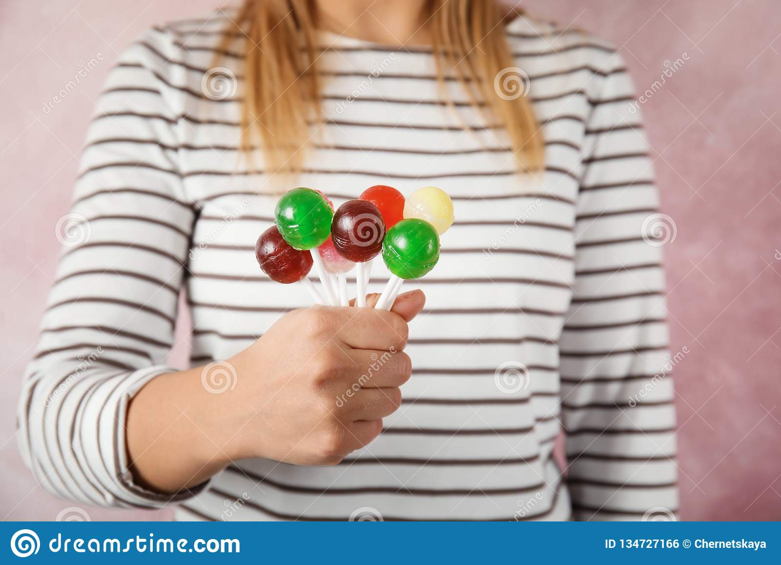 Vrouw die veel kleurrijk lollysuikergoed op kleurenachtergrond houden