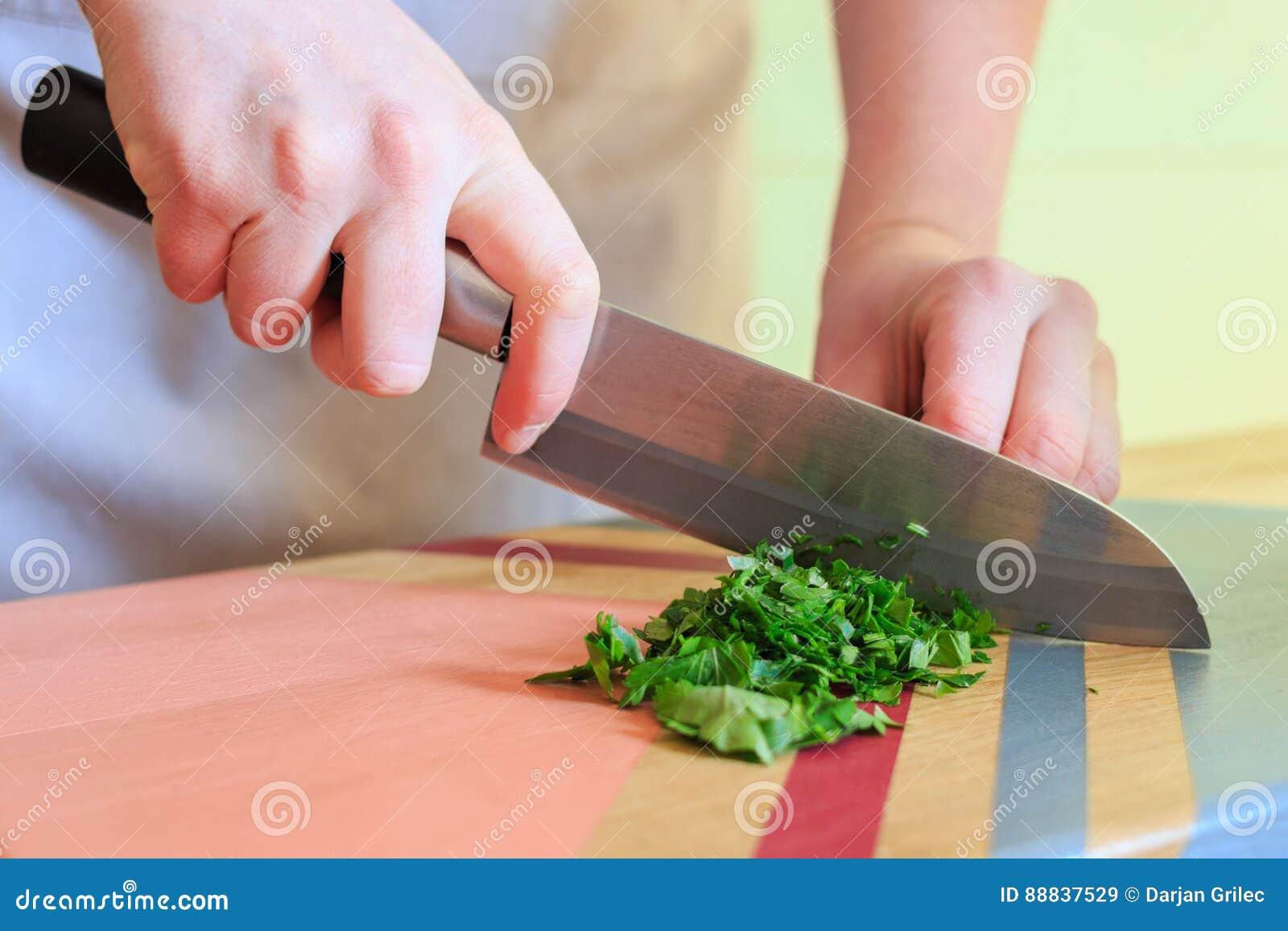 Vrouw die verse peterselie met een groot mes op kleurrijke houten raad snijden