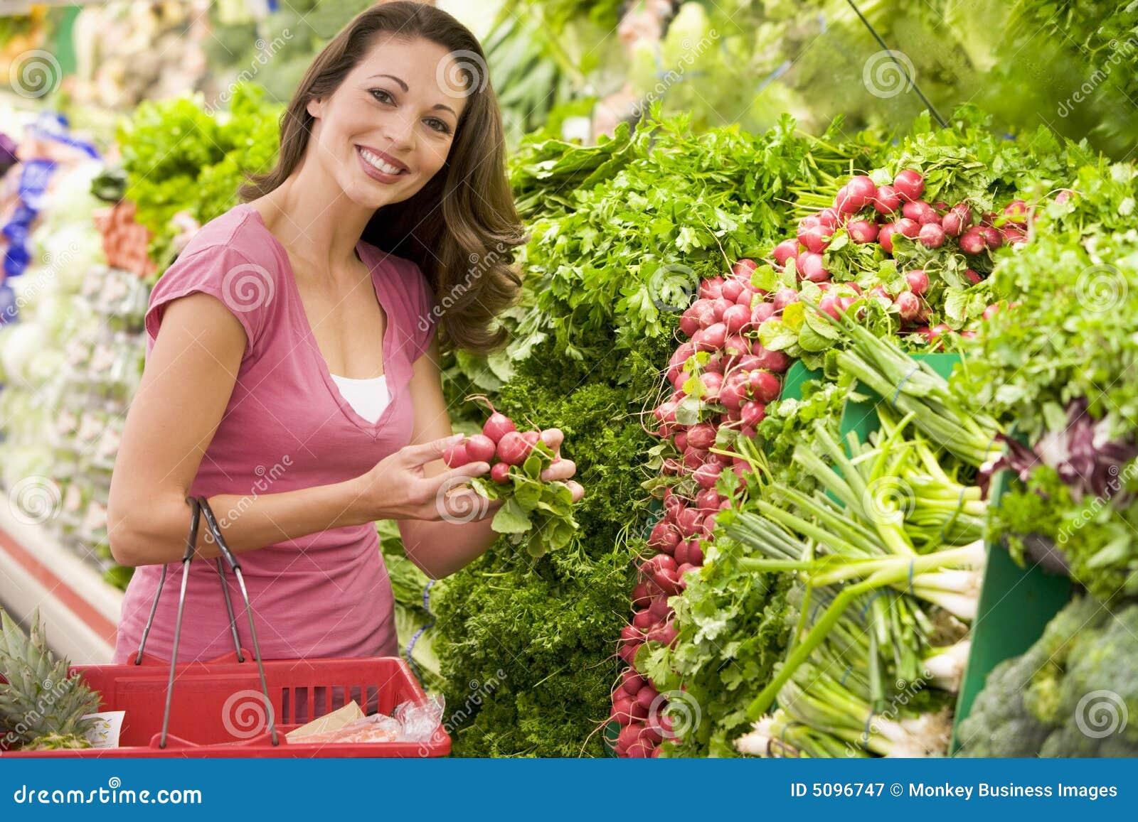 Vrouw die voor opbrengst in supermarkt winkelt