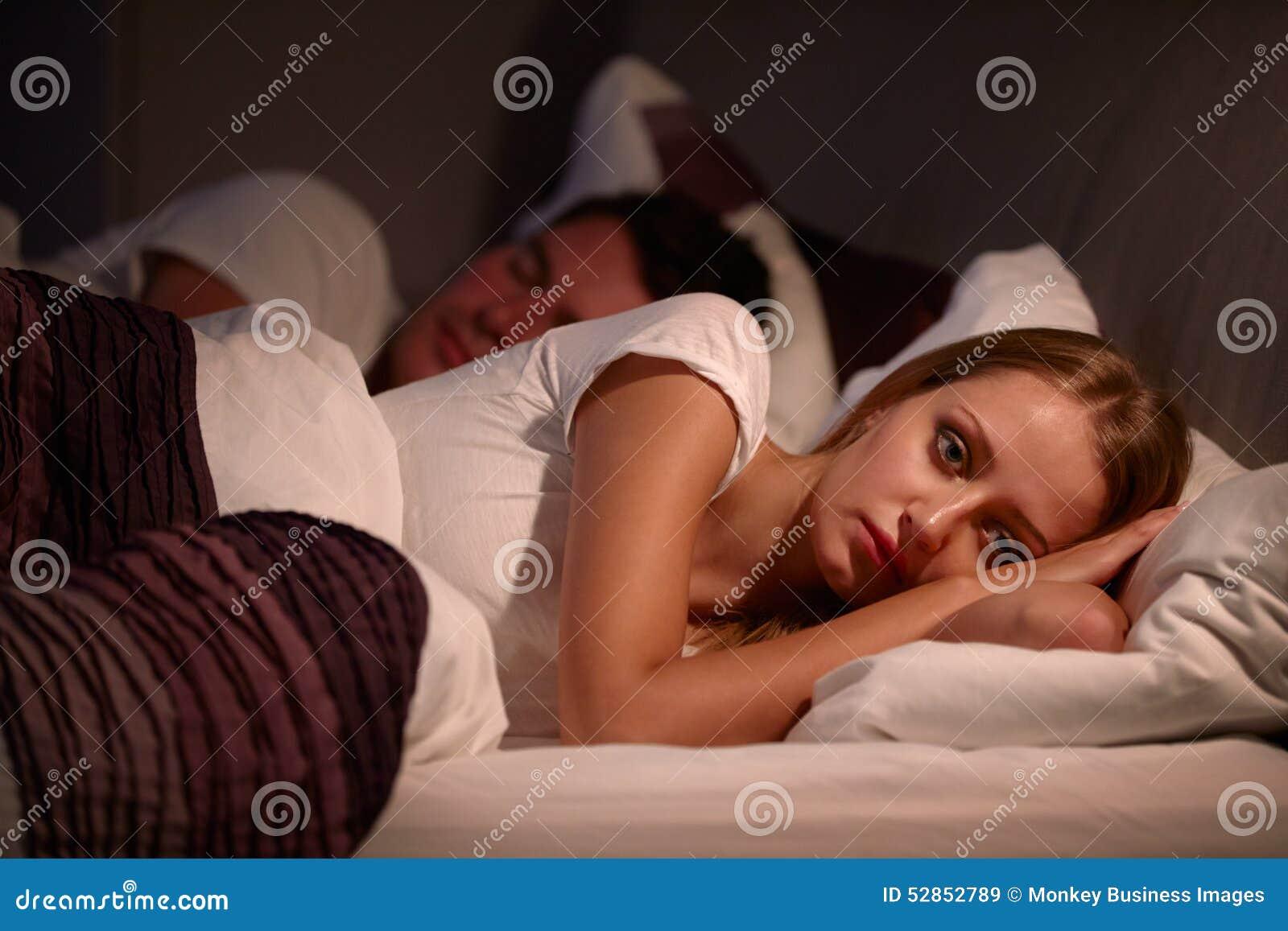 Vrouw die Wakker in Bed liggen die met Slapeloosheid lijden