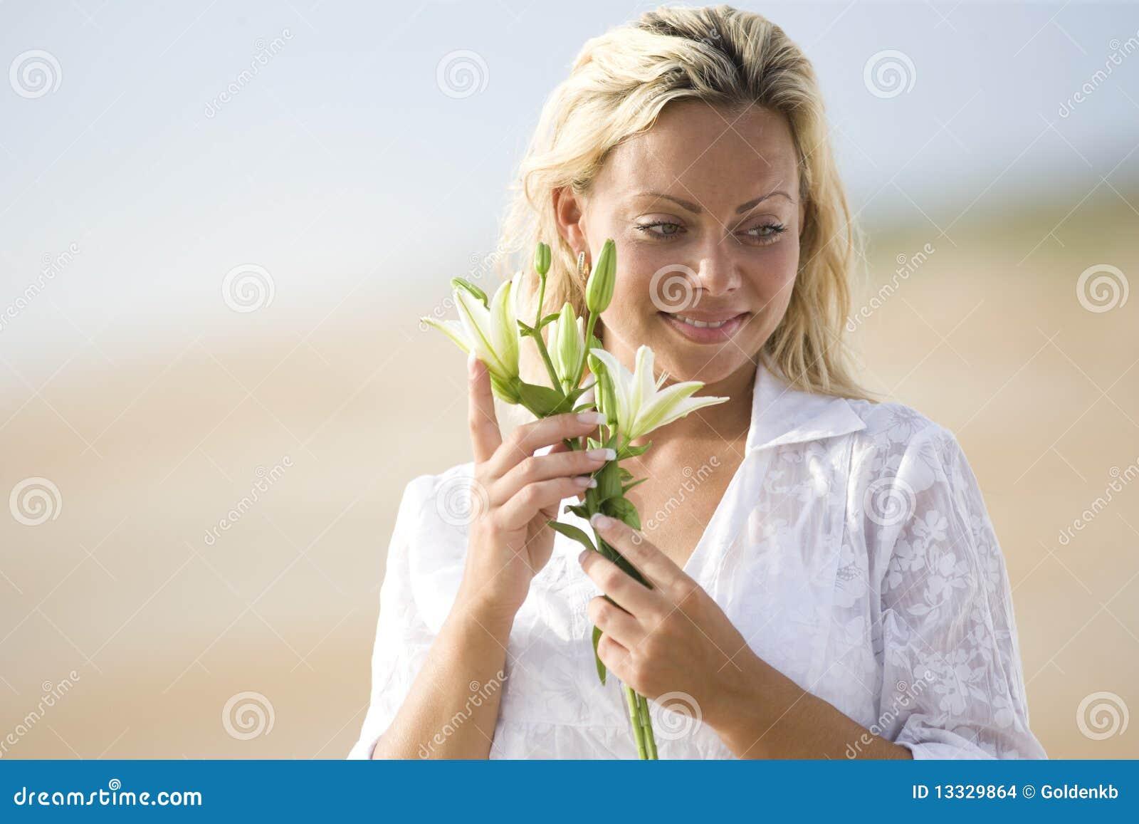 Vrouw die wit op de bloem van de strandholding draagt
