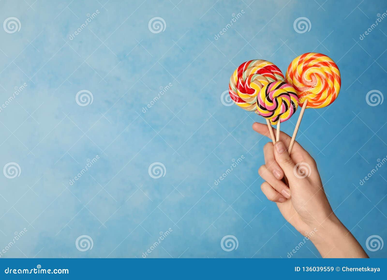 Vrouw die yummy suikergoed op kleurenachtergrond houden
