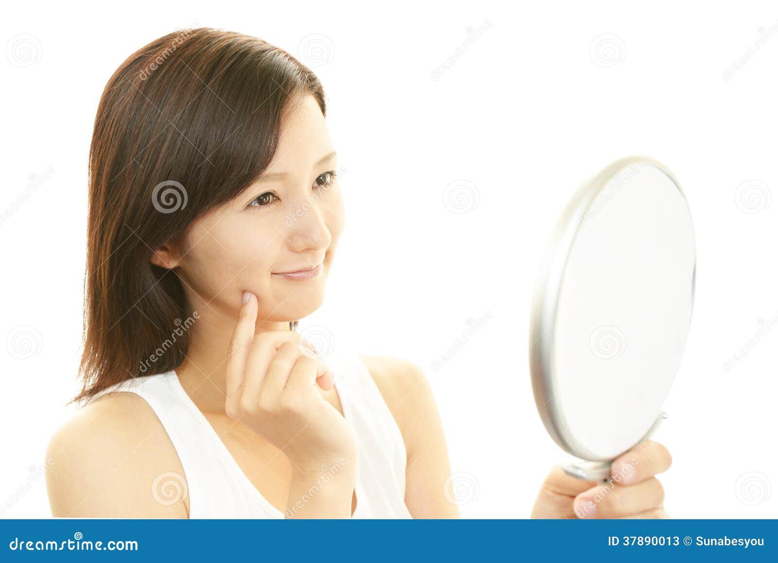 Vrouw die zich in een handspiegel bekijken