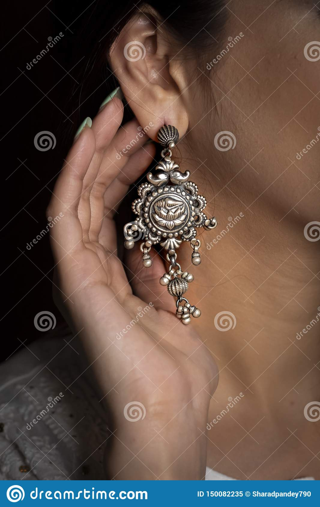 Vrouw die zilveren oorring op oor met hand het tonen draagt