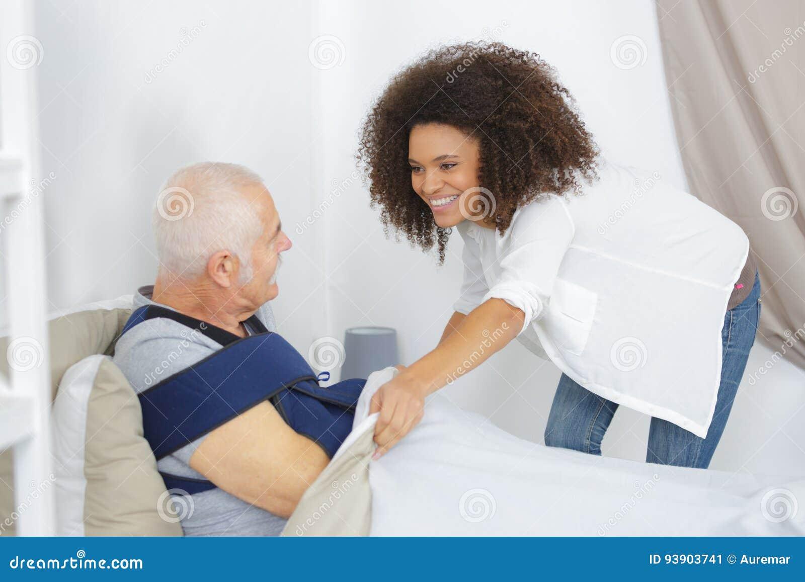 Vrouw die zorgbejaarde in verpleeghuis nemen