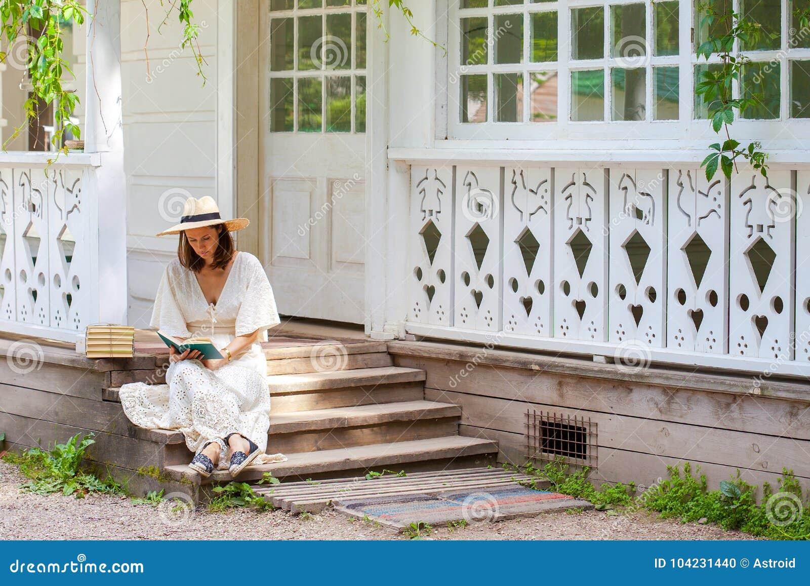 Vrouw in een witte kleding en een strohoed die een boek op por lezen