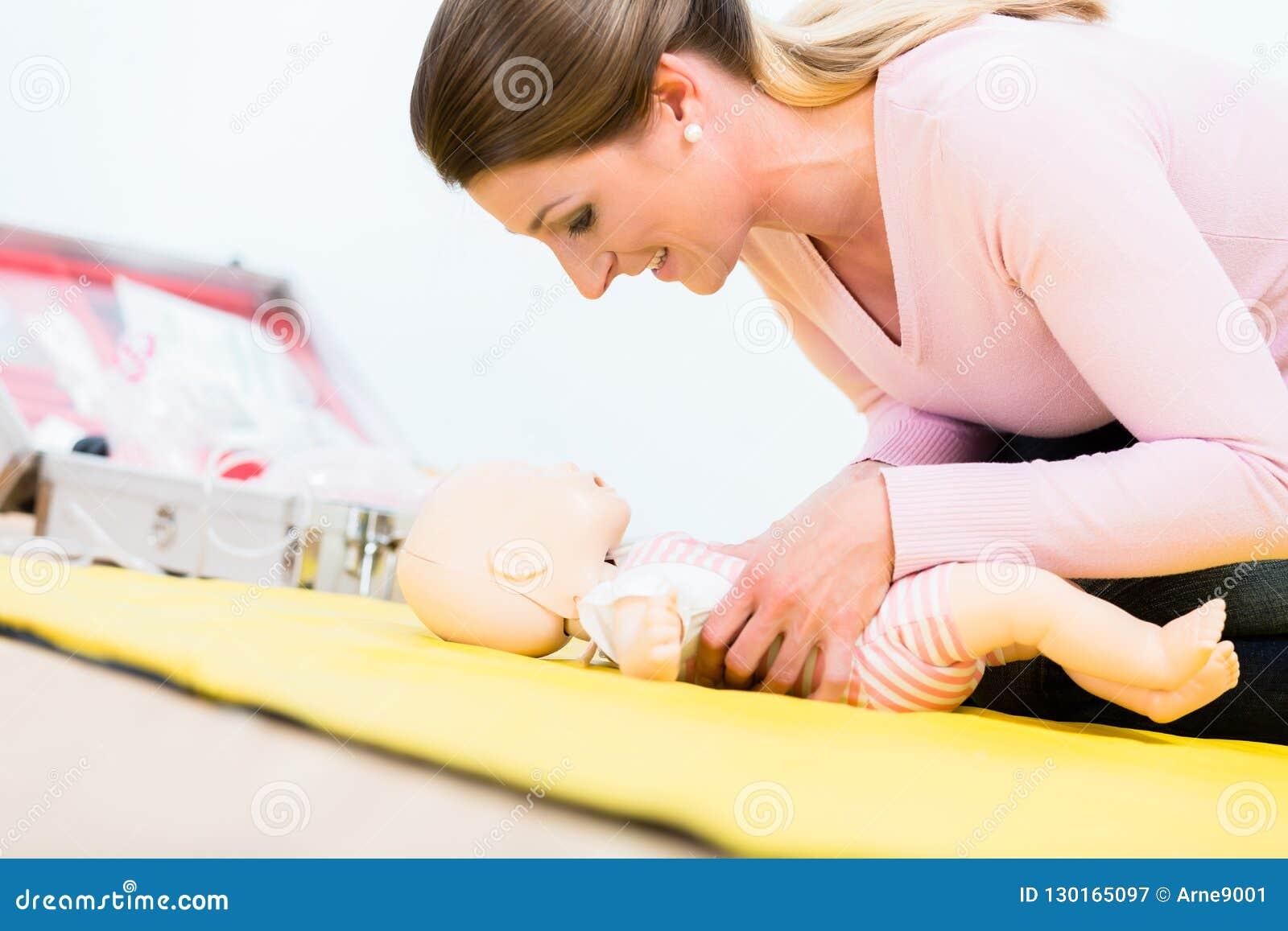 Vrouw in eerste hulpcursus het praktizeren heropleving van zuigeling op baby D