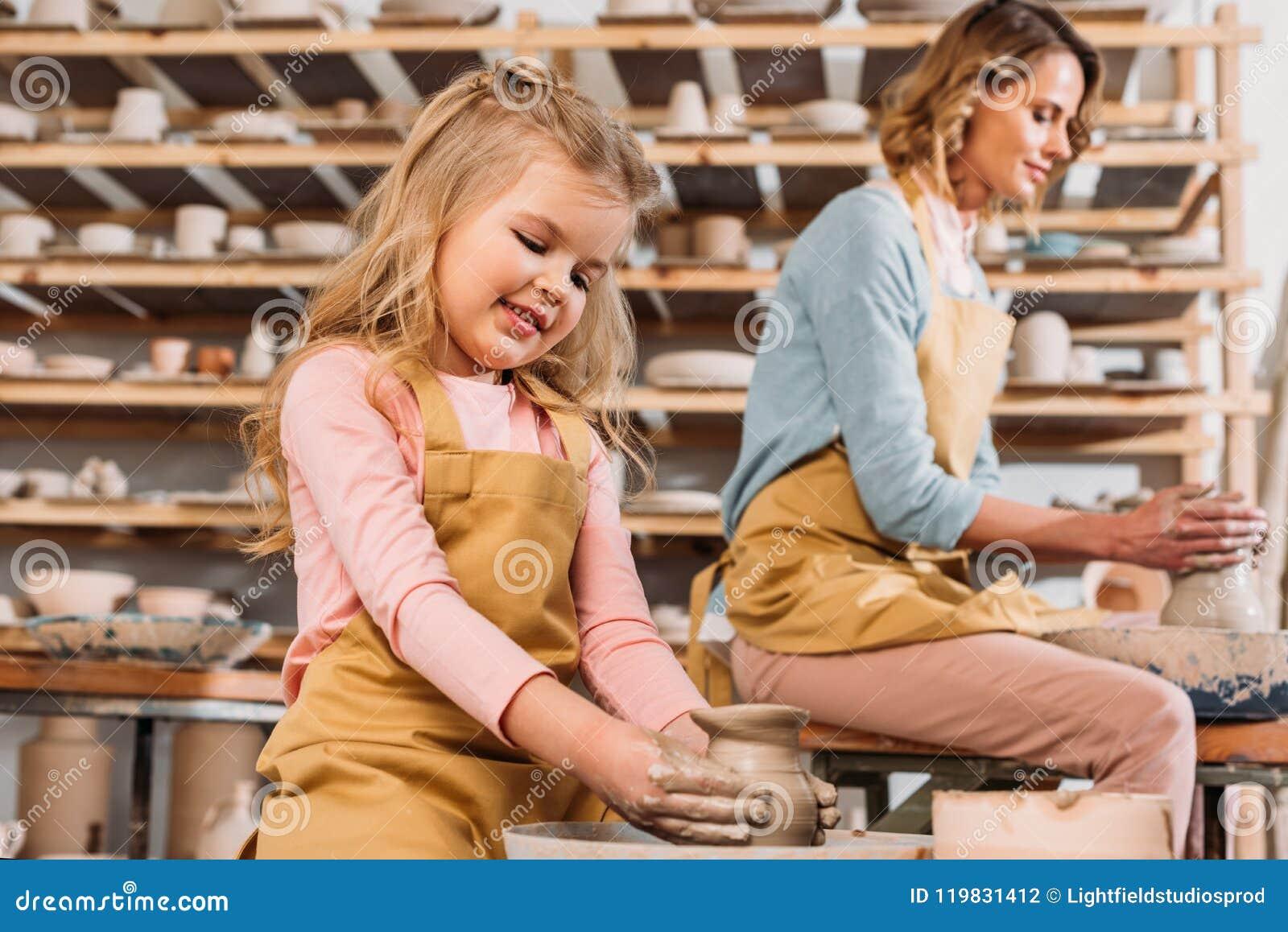 Vrouw en jong geitje die ceramische potten op aardewerkwielen maken