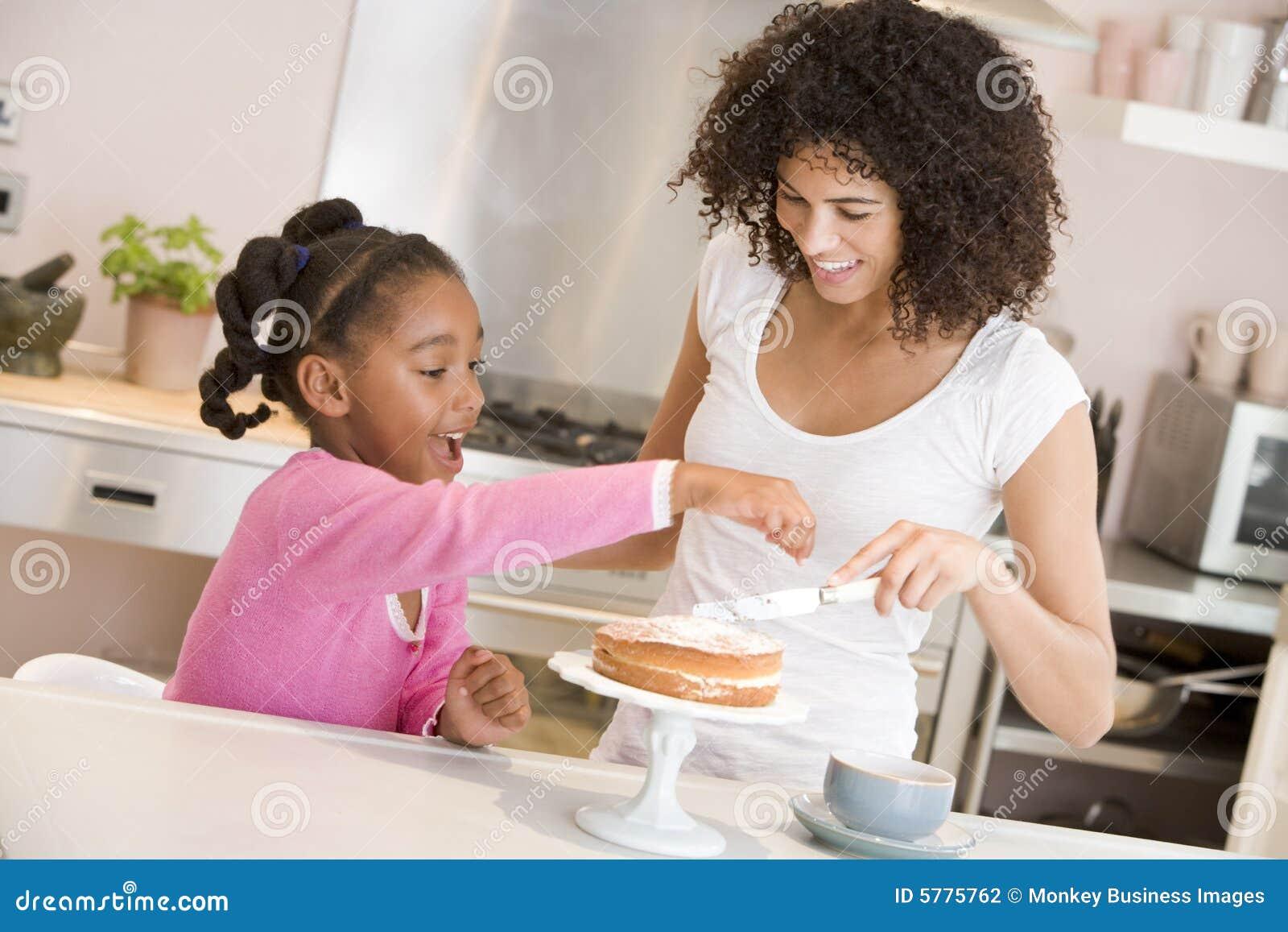 Vrouw en jong meisje in keuken die een cakesmili bevriest