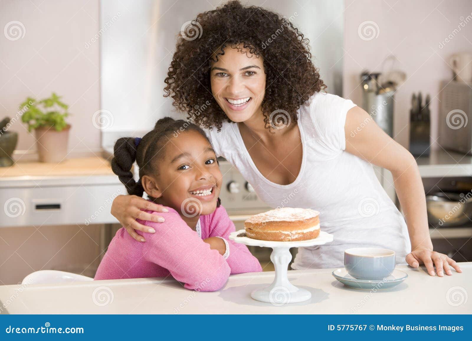 Vrouw en jong meisje in keuken met cake en coff