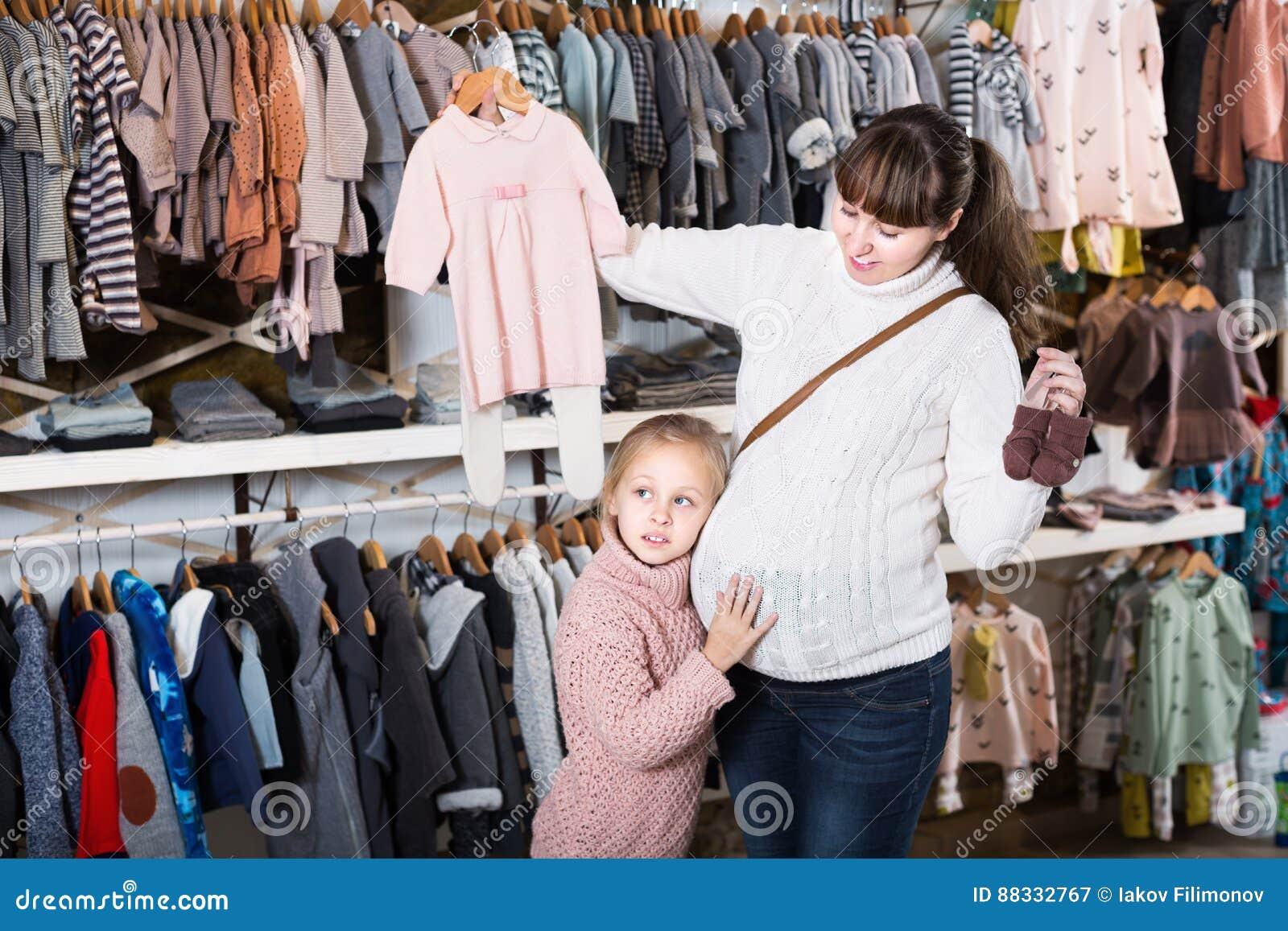 Kleding Zoeken.Vrouw En Kind Die Kleding Zoeken Naar Baby In Winkel Stock