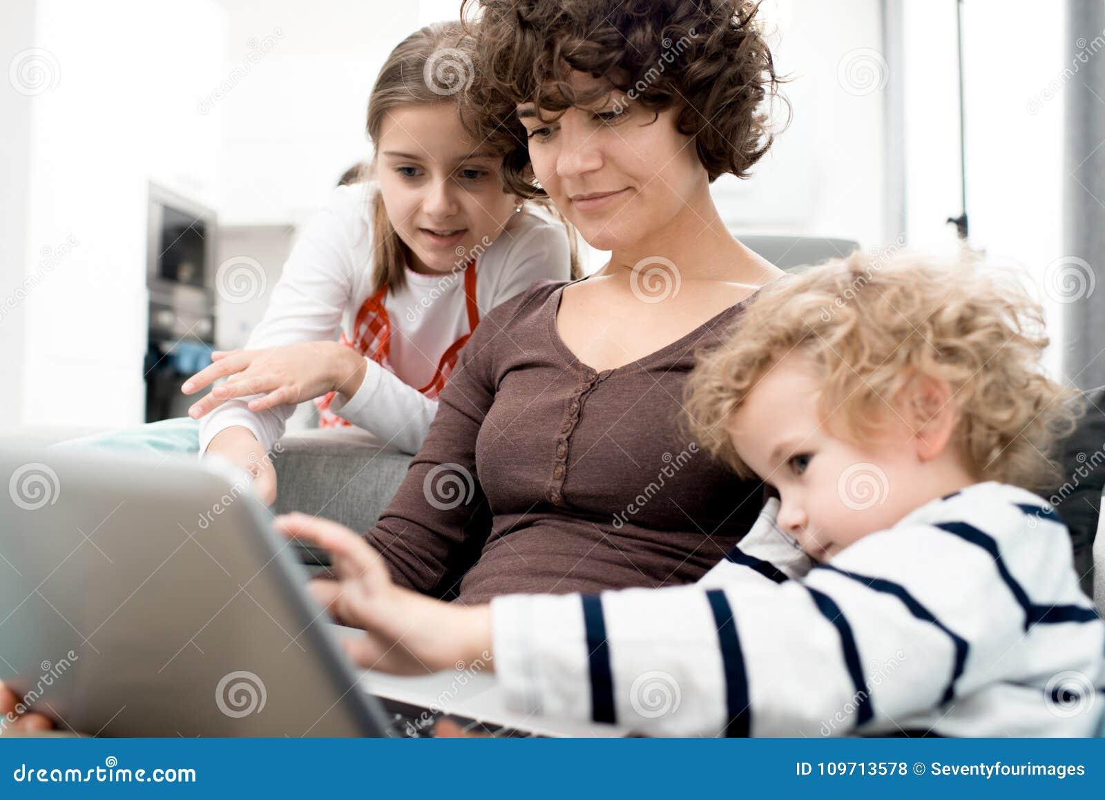Vrouw en Kinderen die Laptop met behulp van