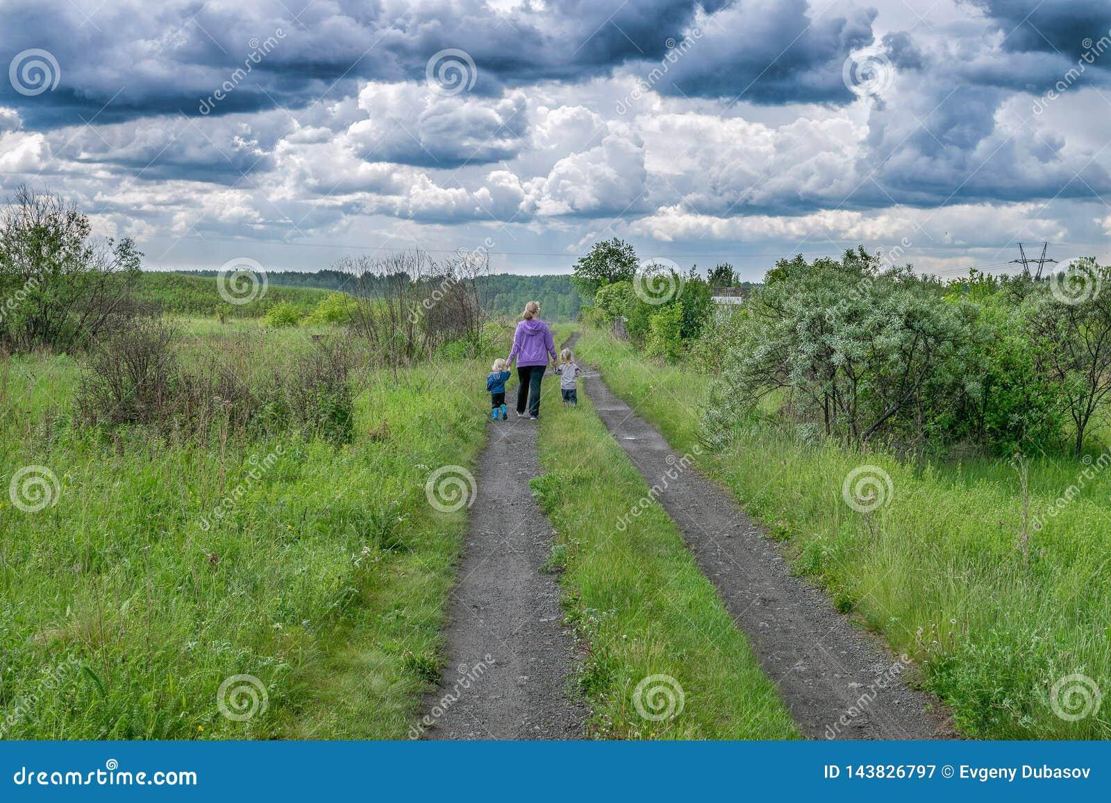 Vrouw en kinderengang op weg onder donkere wolken