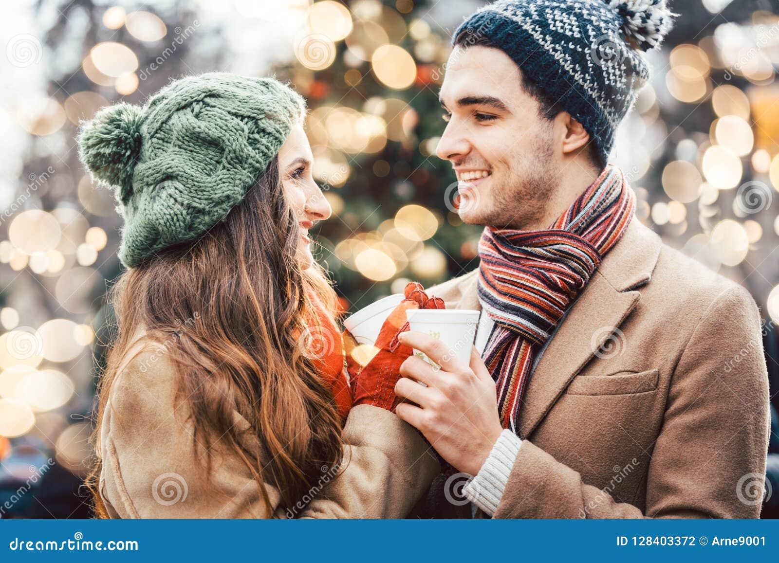 Vrouw en man die overwogen wijn op Kerstmismarkt drinken