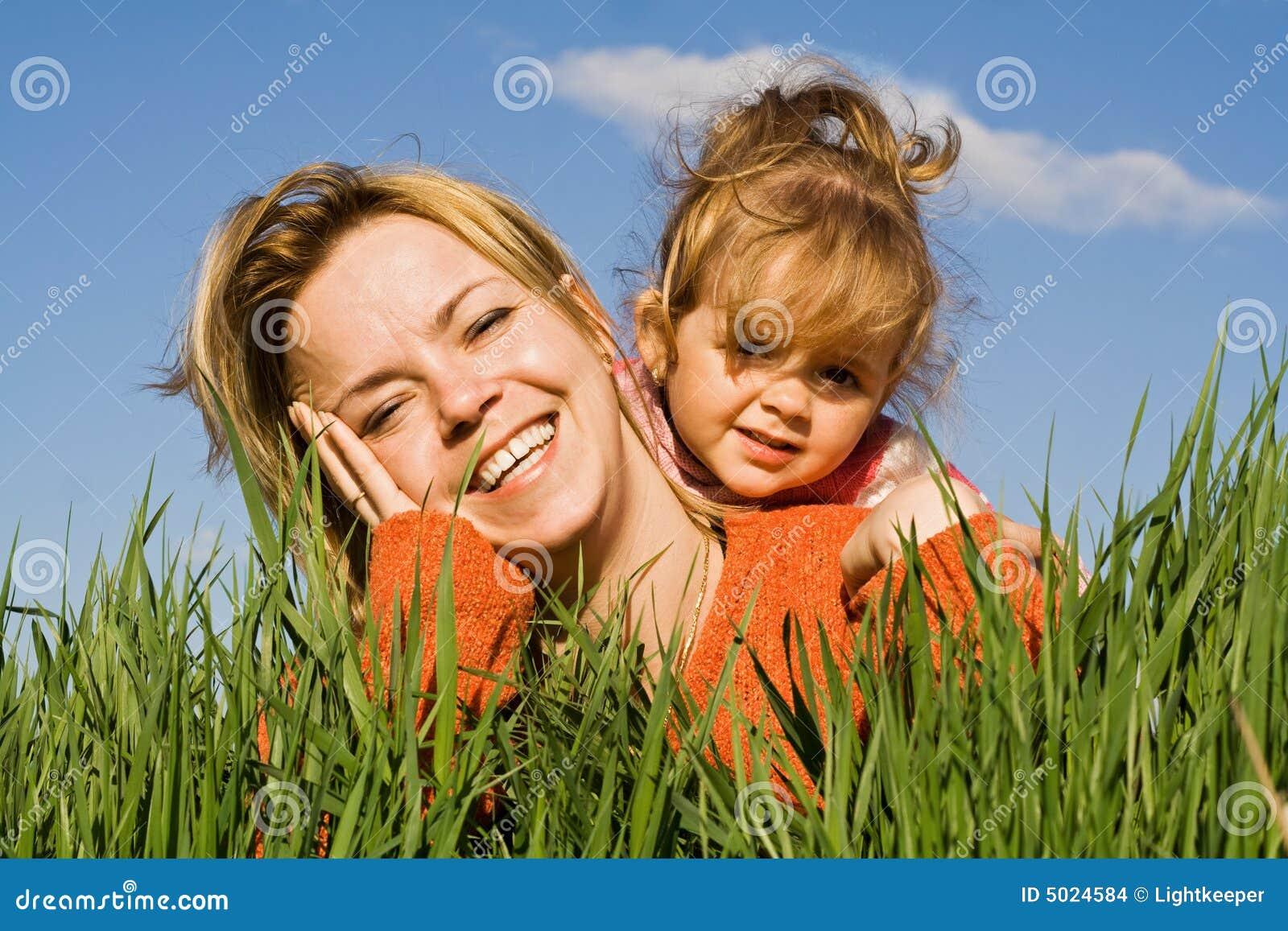 Vrouw en meisje in het gras