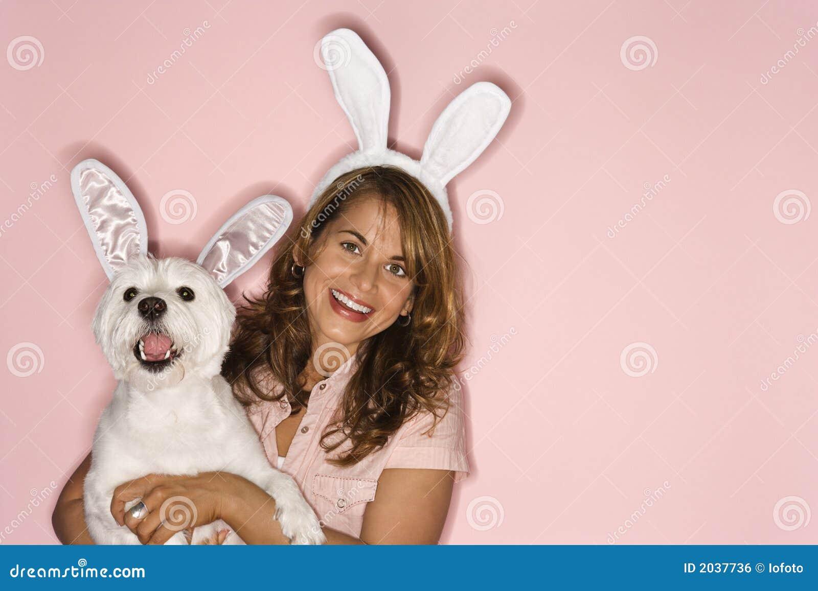 Vrouw en witte hond die konijnoren dragen.