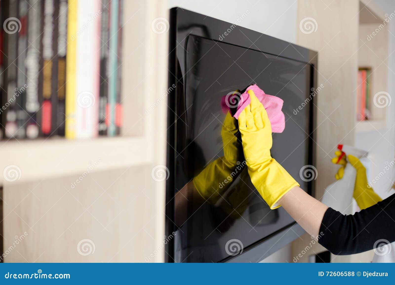 Vrouw in gele rubberhandschoenen die TV schoonmaken