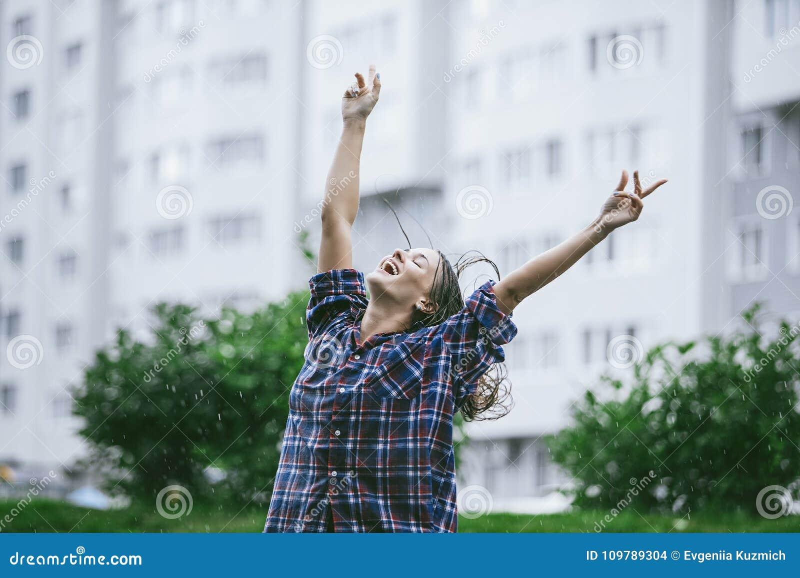Vrouw gelukkige het glimlachen gelukhanden uitgestrekt naar de regen