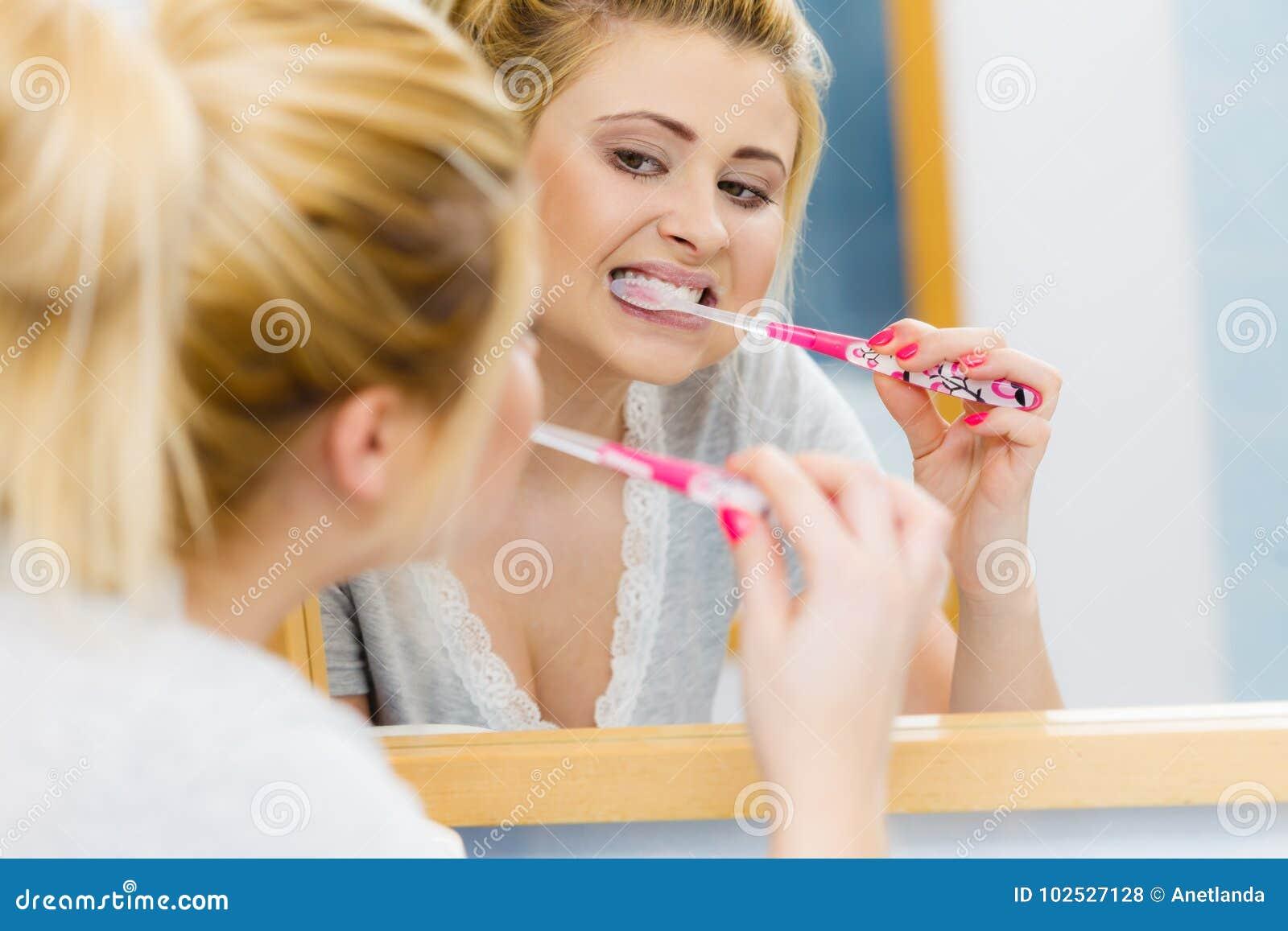 Vrouw het borstelen schoonmakende tanden in badkamers