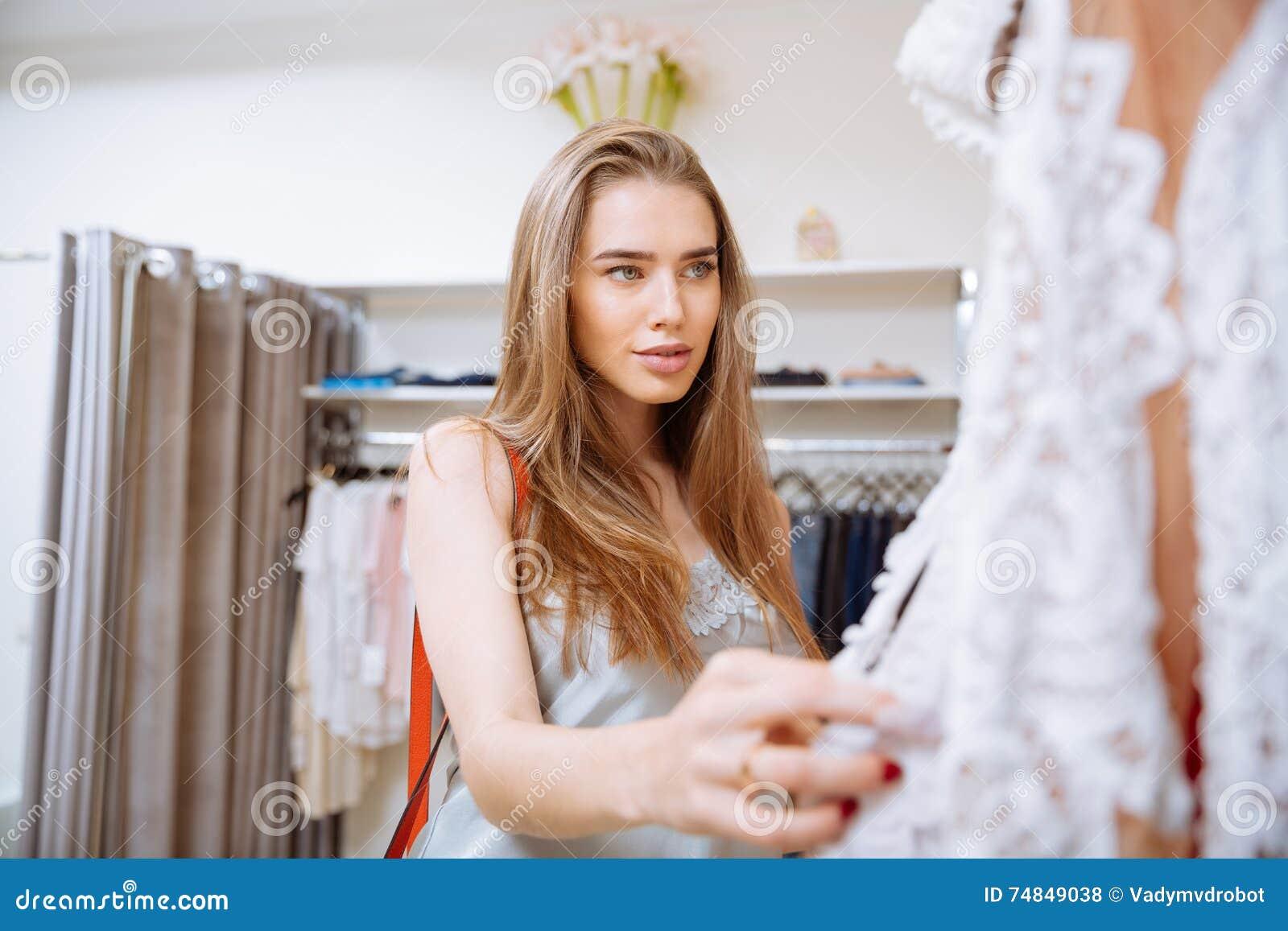7646590c672272 Het aantrekkelijke jonge vrouw doen winkelend en kiezend kleren in  kledingsopslag