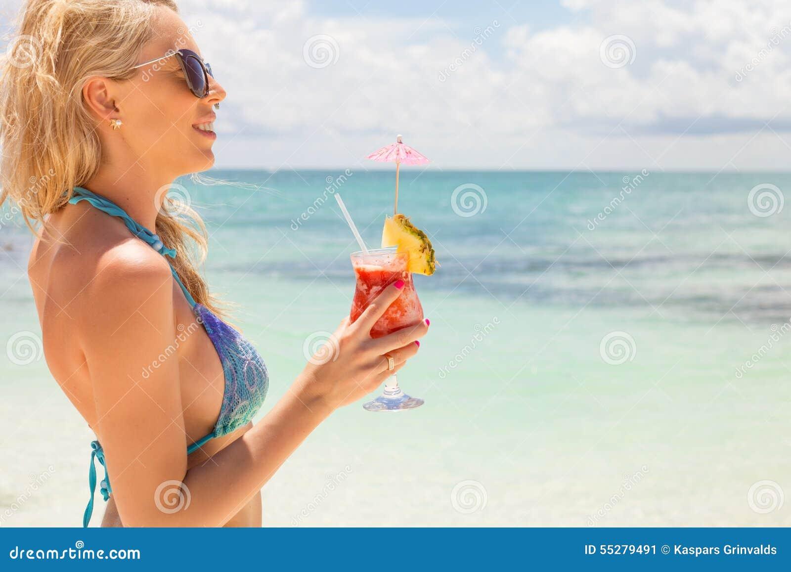 Vrouw het drinken de cocktail van aardbeimargarita op het strand