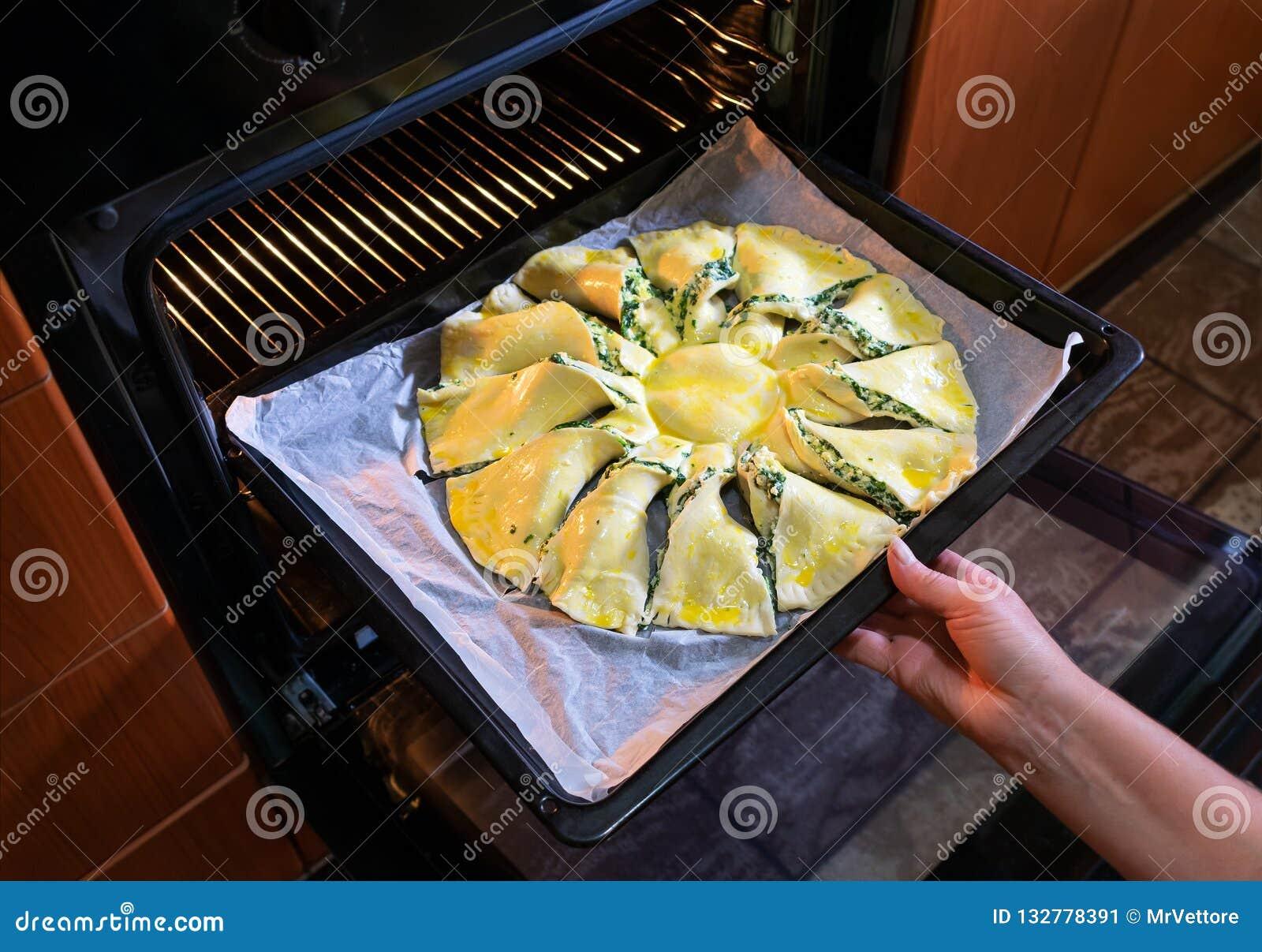 Vrouw het koken in de keuken zet een ruwe pastei in de oven De mening van de close-up