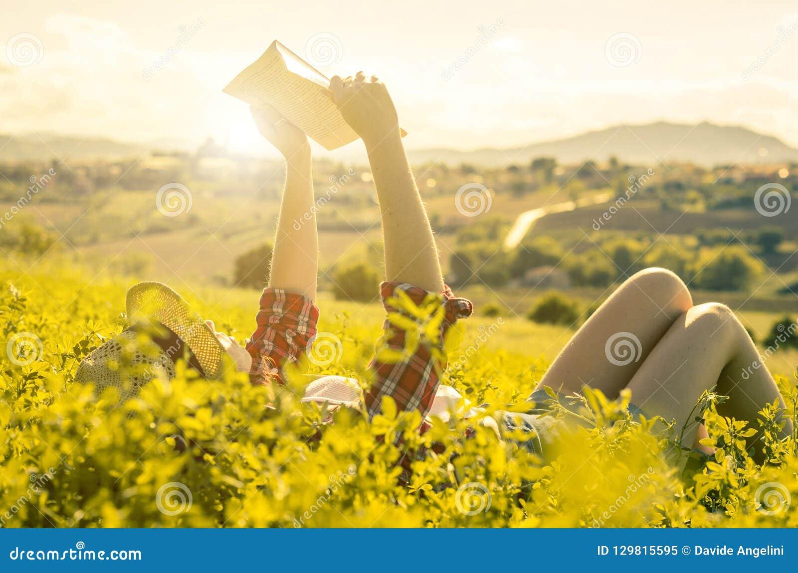 Vrouw het liggen op het gras las een boek in het platteland