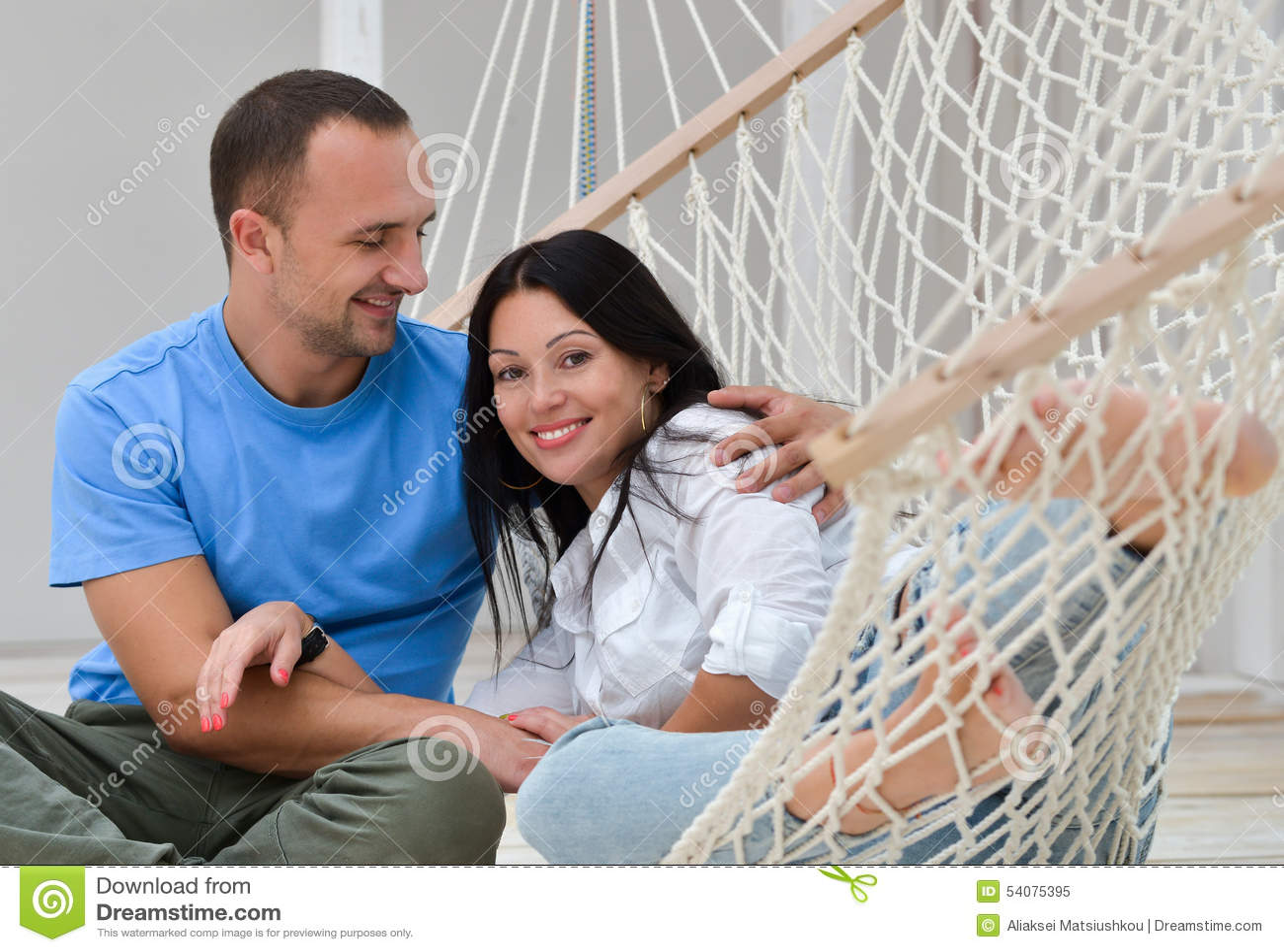Vrouw het ontspannen in hangmat het glimlachen en man zitting
