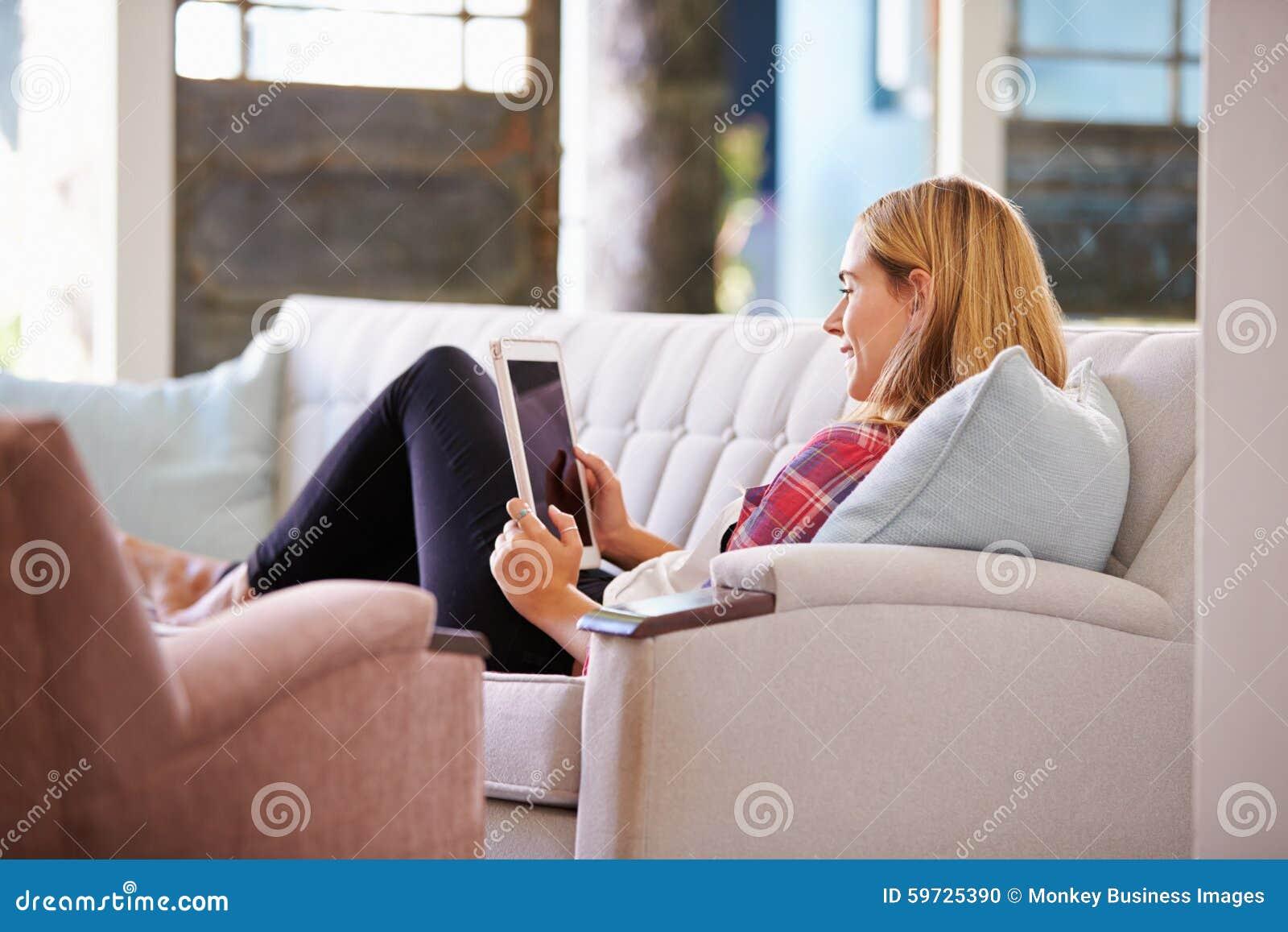 Vrouw het Ontspannen op Sofa At Home Using Digital-Tablet