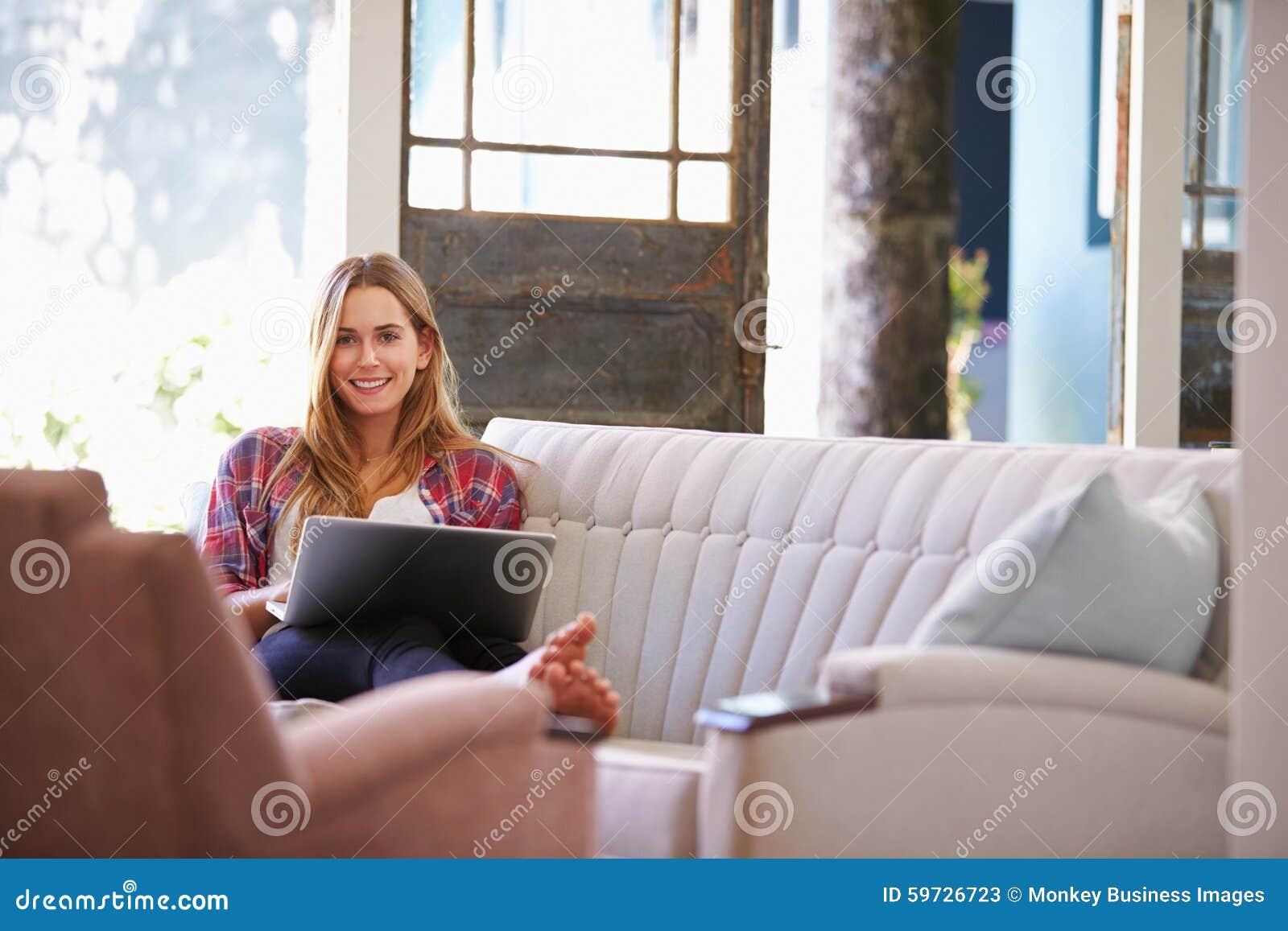 Vrouw het Ontspannen op Sofa At Home Using Laptop-Computer