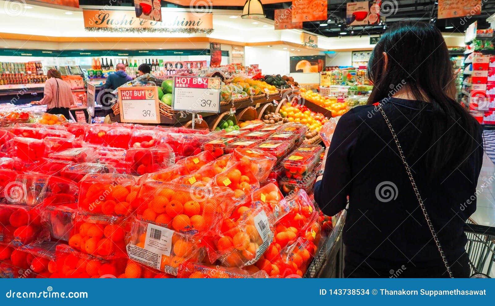 Vrouw het selecteren fruit vers in de opbrengsafdeling van de kruidenierswinkelopslag en het zetten van het in plastic zak Het jo