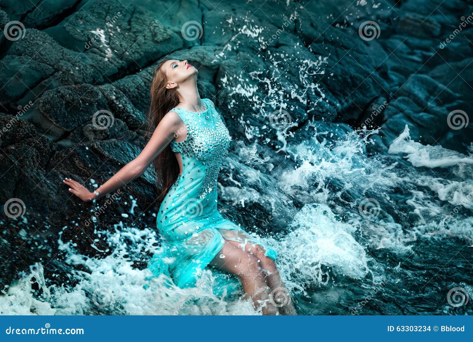 Vrouw het stellen op een strand met rotsen
