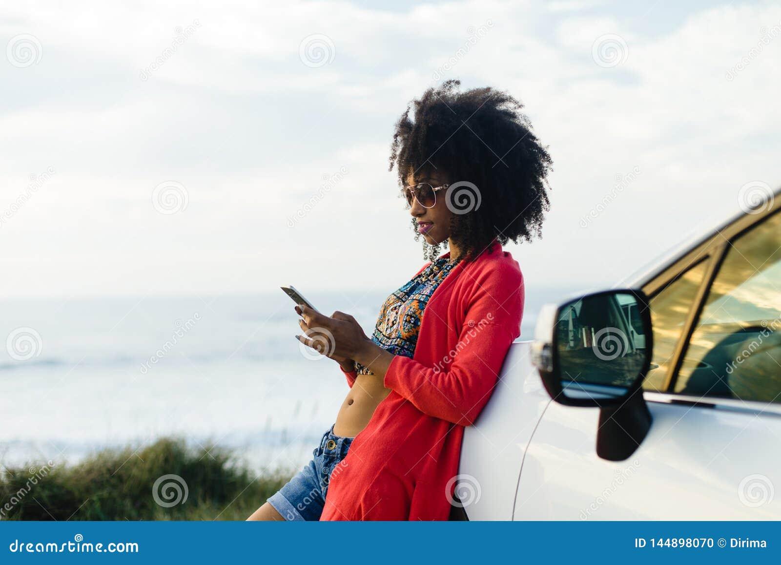 Vrouw het texting op haar telefoon tijdens autoreis aan de kust