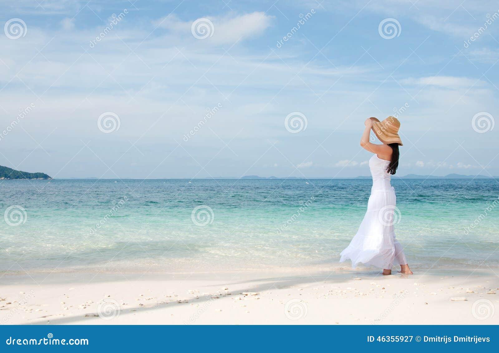 Vrouw in hoed op oever bij het tropische strand