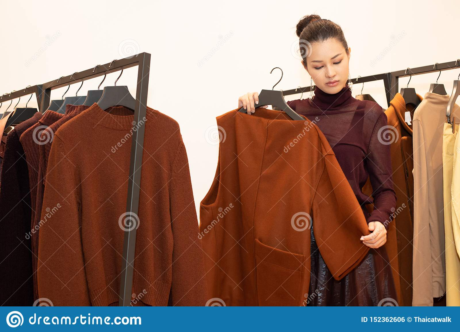 Vrouw in kledings uitgezochte nieuwe inzameling op rek