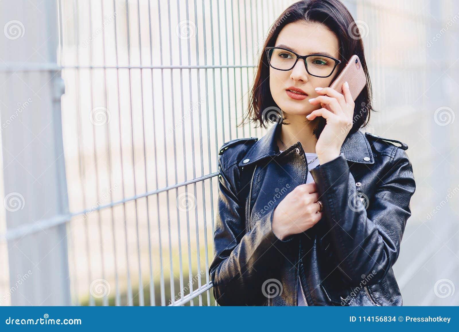 Vrouw in leerjasje in glazen die op telefoon spreken