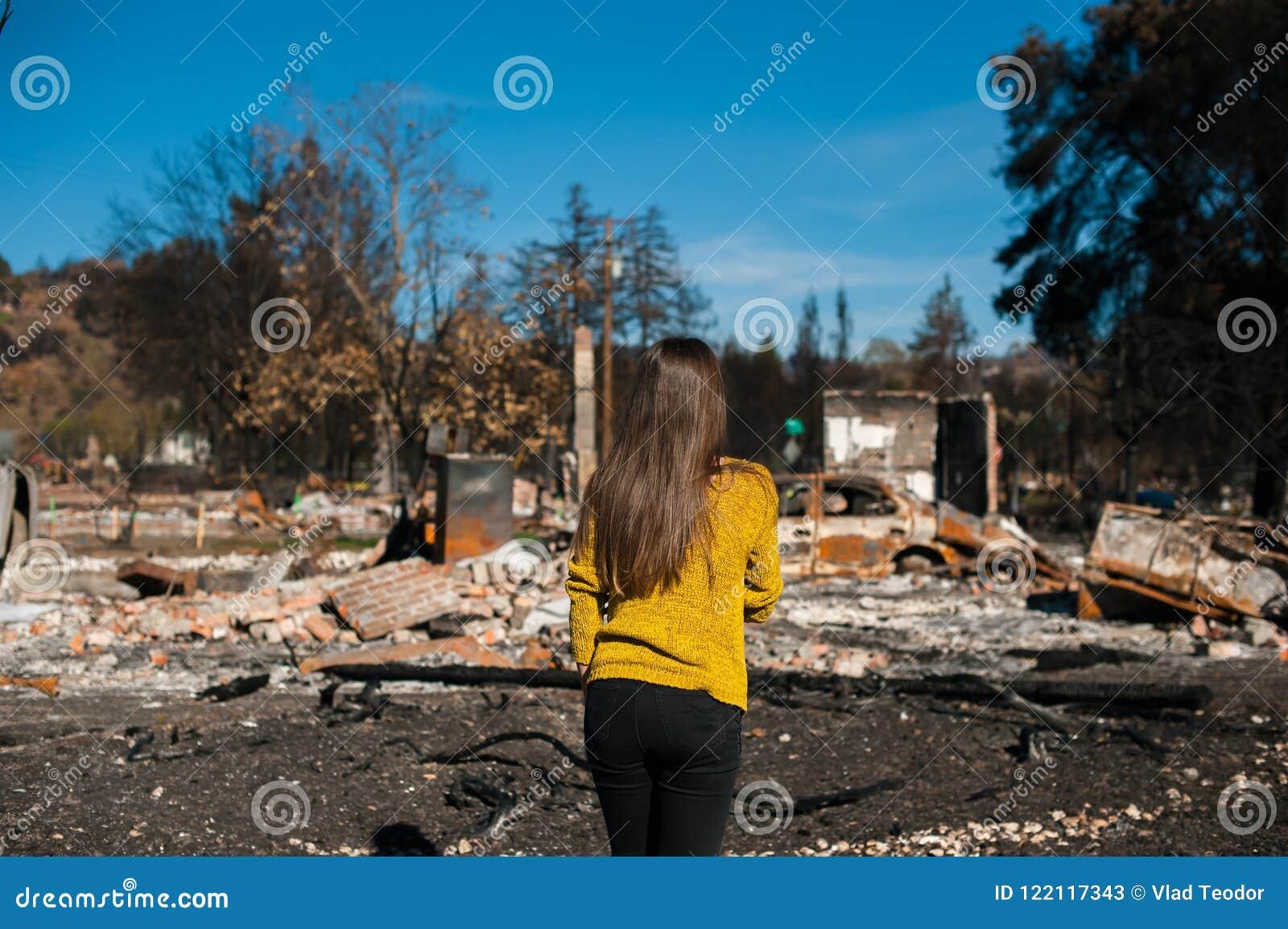 Vrouw lookinh bij haar gebrand huis na brandramp