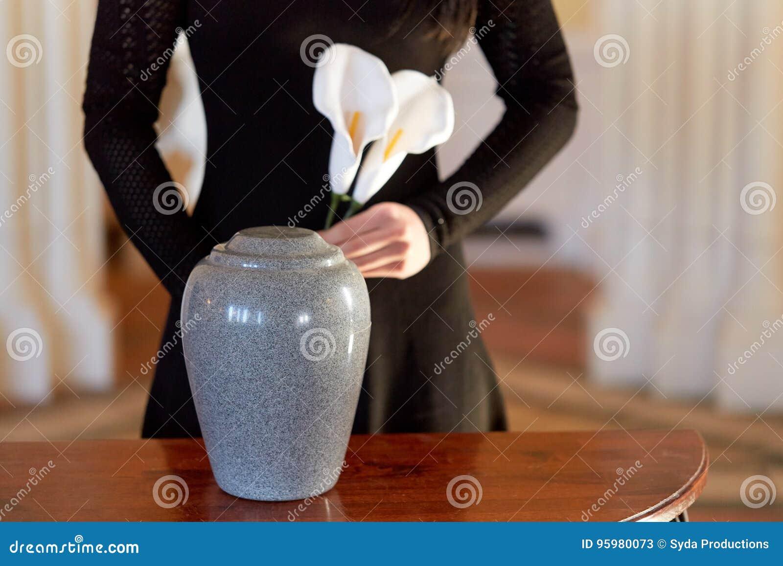 Vrouw met crematieurn bij begrafenis in kerk